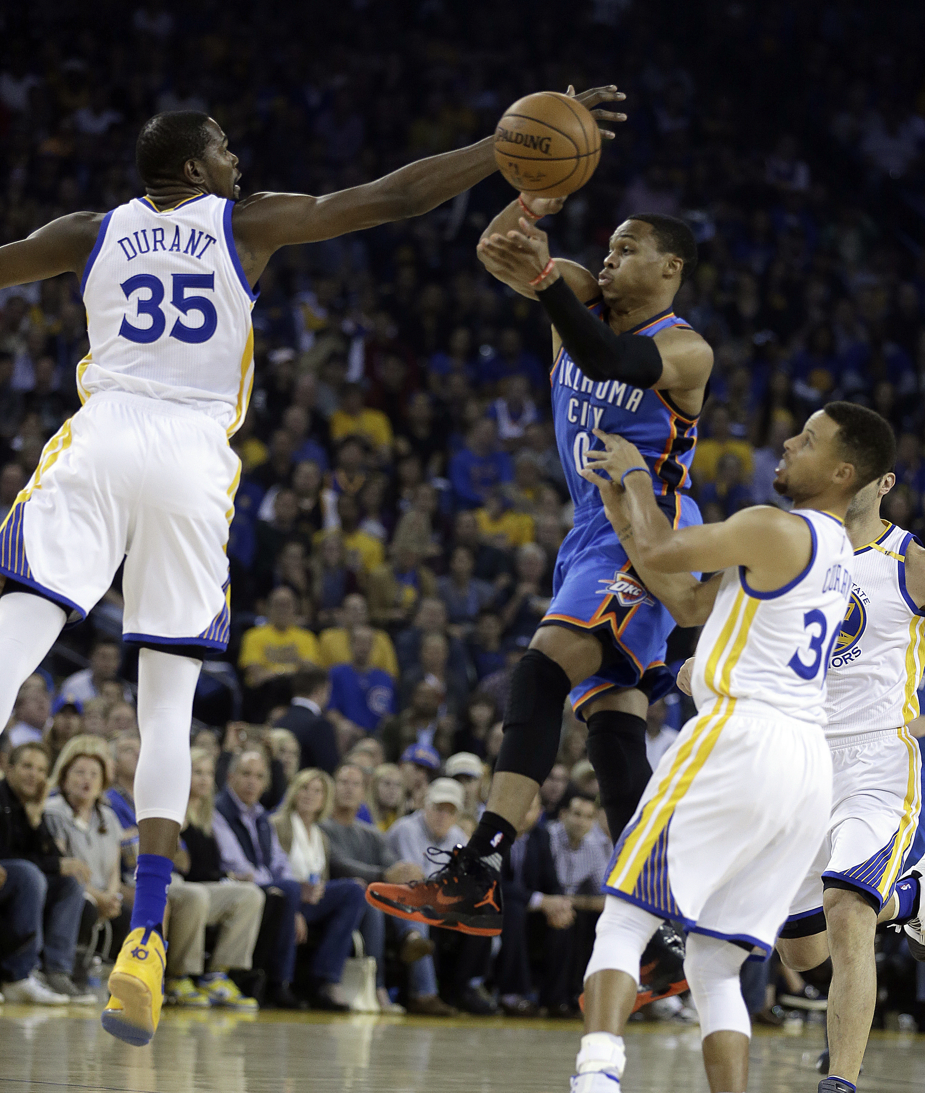 Oklahoma City Thunder guard Russell Westbrook, right, passes away from Golden State Warriors' Kevin Durant (35) during the first half of an NBA basketball game Thursday, Nov. 3, 2016, in Oakland, Calif.