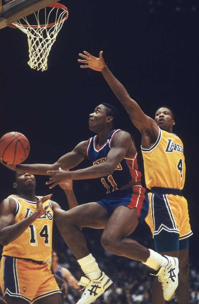 a7b1e3fe42f1 Detroit Pistons  Isiah Thomas (11) goes up for a basket as Los Angeles  Lakers  Sam Perkins (14) and Byron Scott (4) try to block at Great Western  Forum in ...