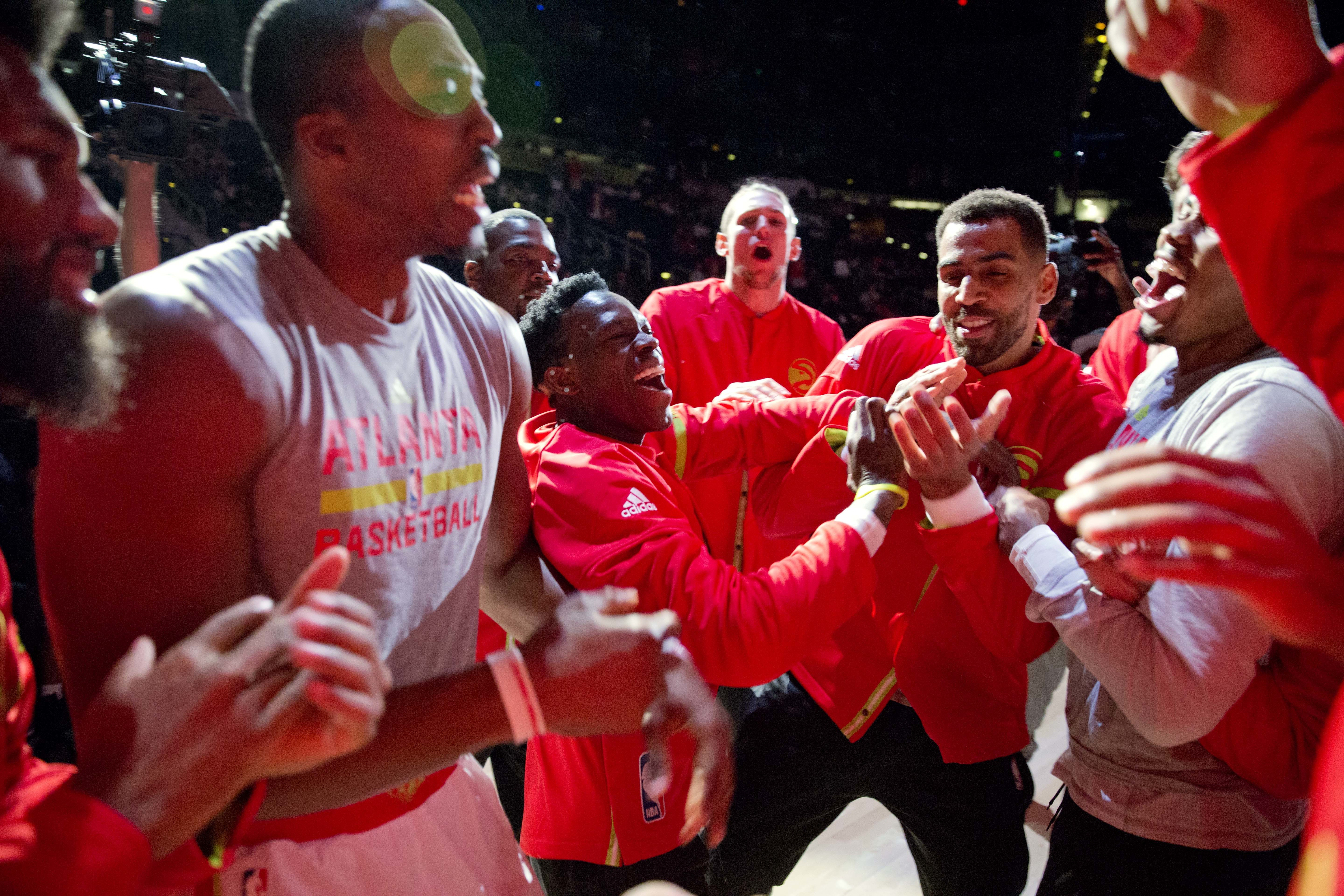 Atlanta Hawks' Dennis Schroder, center left, Thabo Sefolosha, center right, Dwight Howard, left, and fellow teammates cheer in a huddle before the start of an NBA basketball game against the Sacramento Kings in Atlanta, Monday, Oct. 31, 2016.