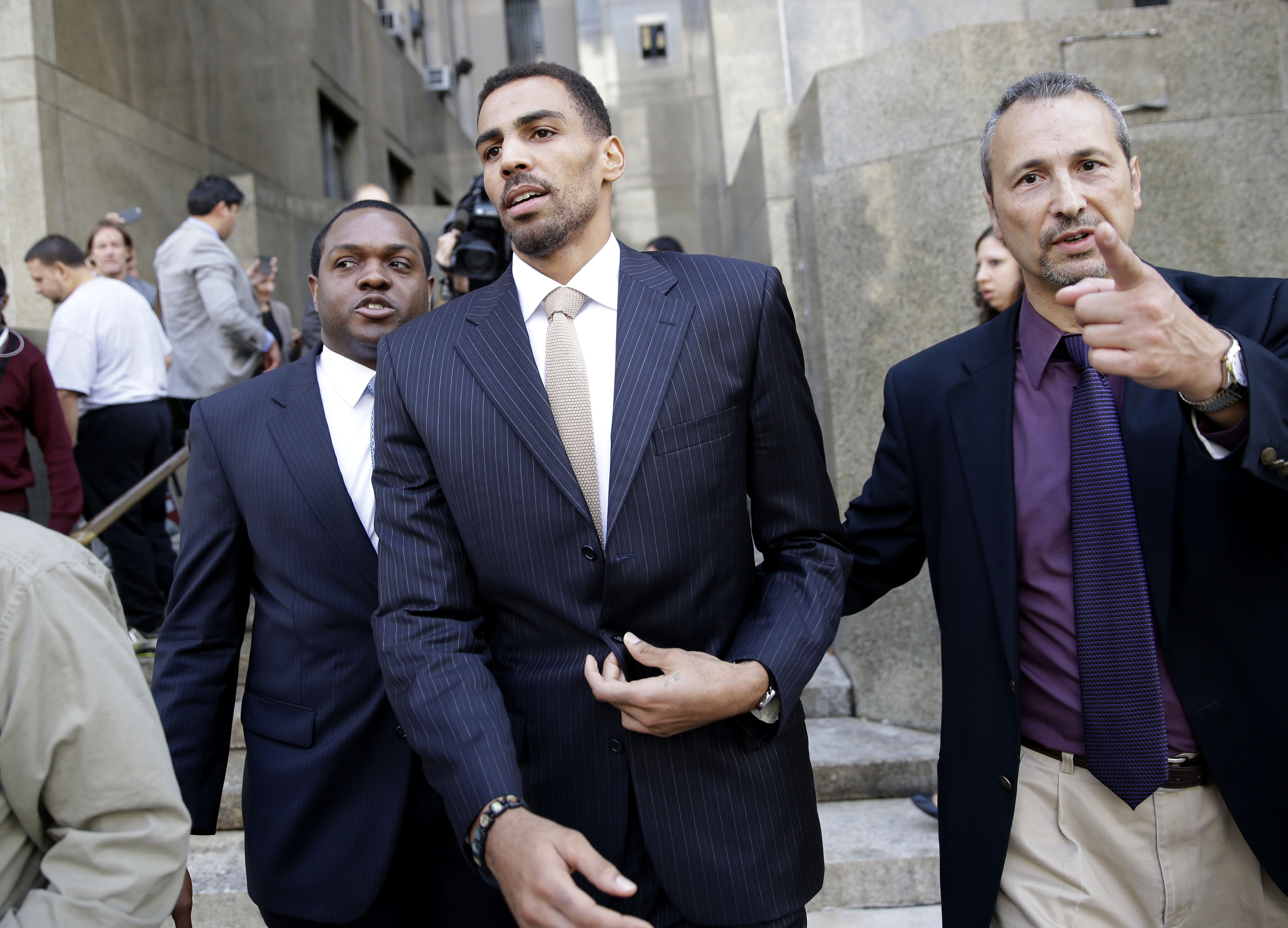 Thabo Sefolosha, center, leaves criminal court in New York, Friday, Oct. 9, 2015. The Atlanta Hawks' player was acquitted Friday in a case stemming from a police fracas outside a trendy New York City nightclub.