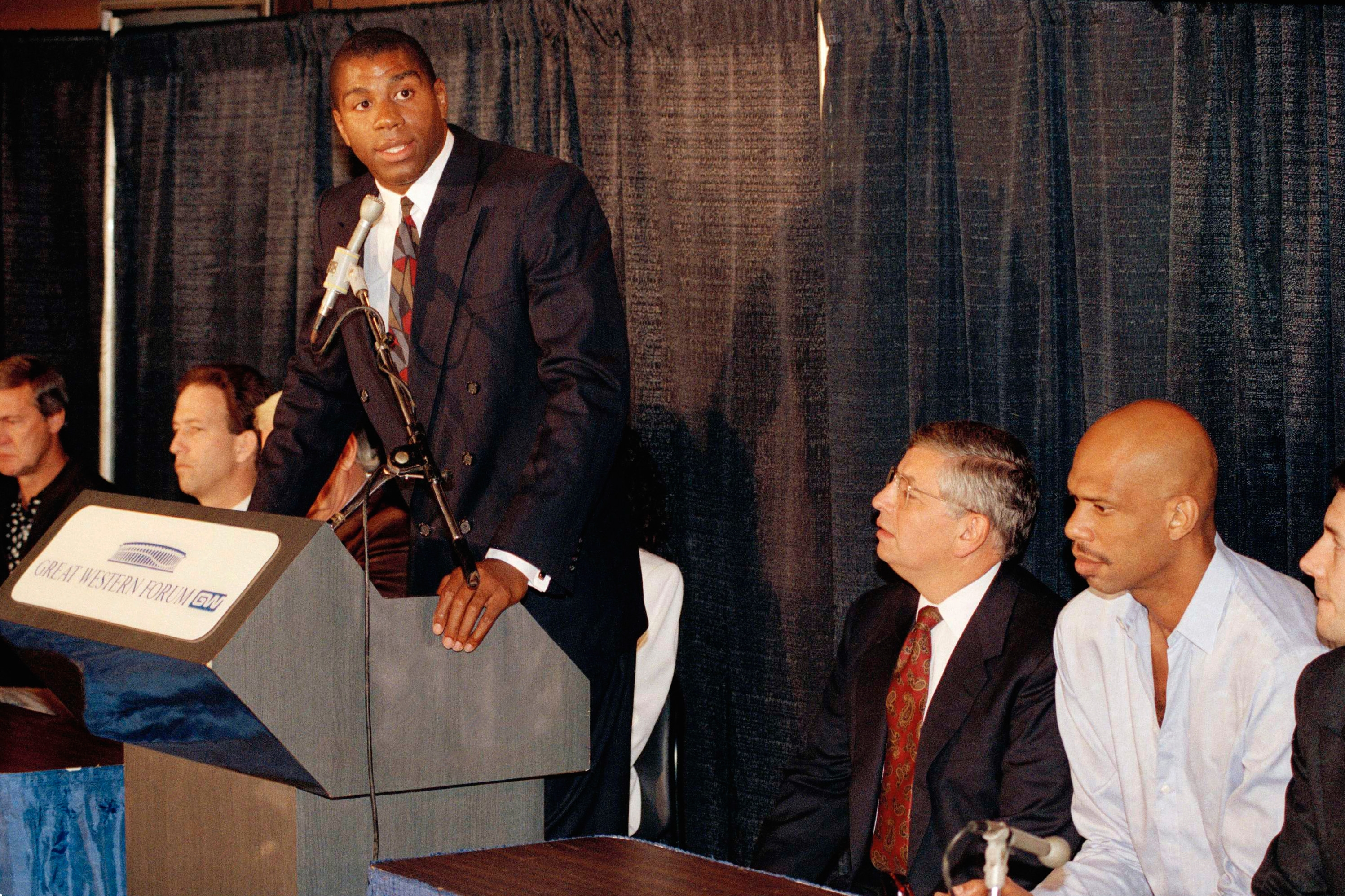 "Earvin ""Magic ' Johnson speaks during a press Conference to announce his retirement from Los Angeles Lakers while former teammate Kareem Abdul Jabbar, right, and NBA Commissioner David Stern, looks on Thursday, Nov. 7, 1991 in Inglewood, Calif. Johnson announced his retirement after learning he had tested postive for the AIDS virus."