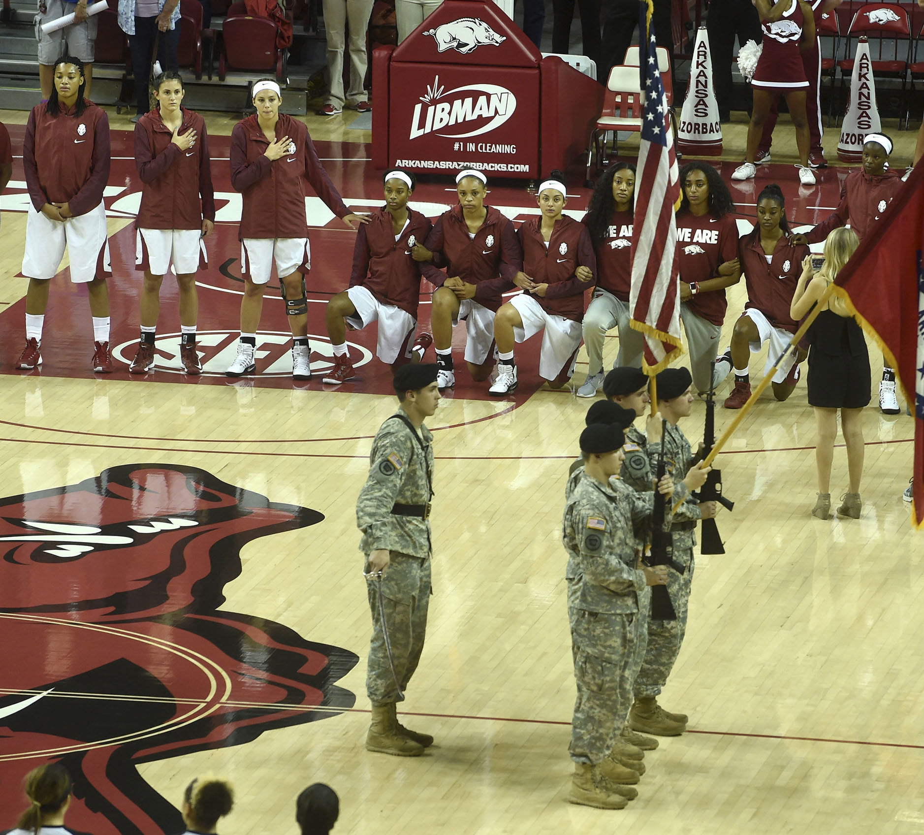 In this Thursday, Nov. 3, 2016 photo, six members of the Arkansas women's basketball team kneel during the national anthem before their exhibition game against Oklahoma Baptist in Fayetteville, Ark. Arkansas athletic director Jeff Long said the university is backing the six players.