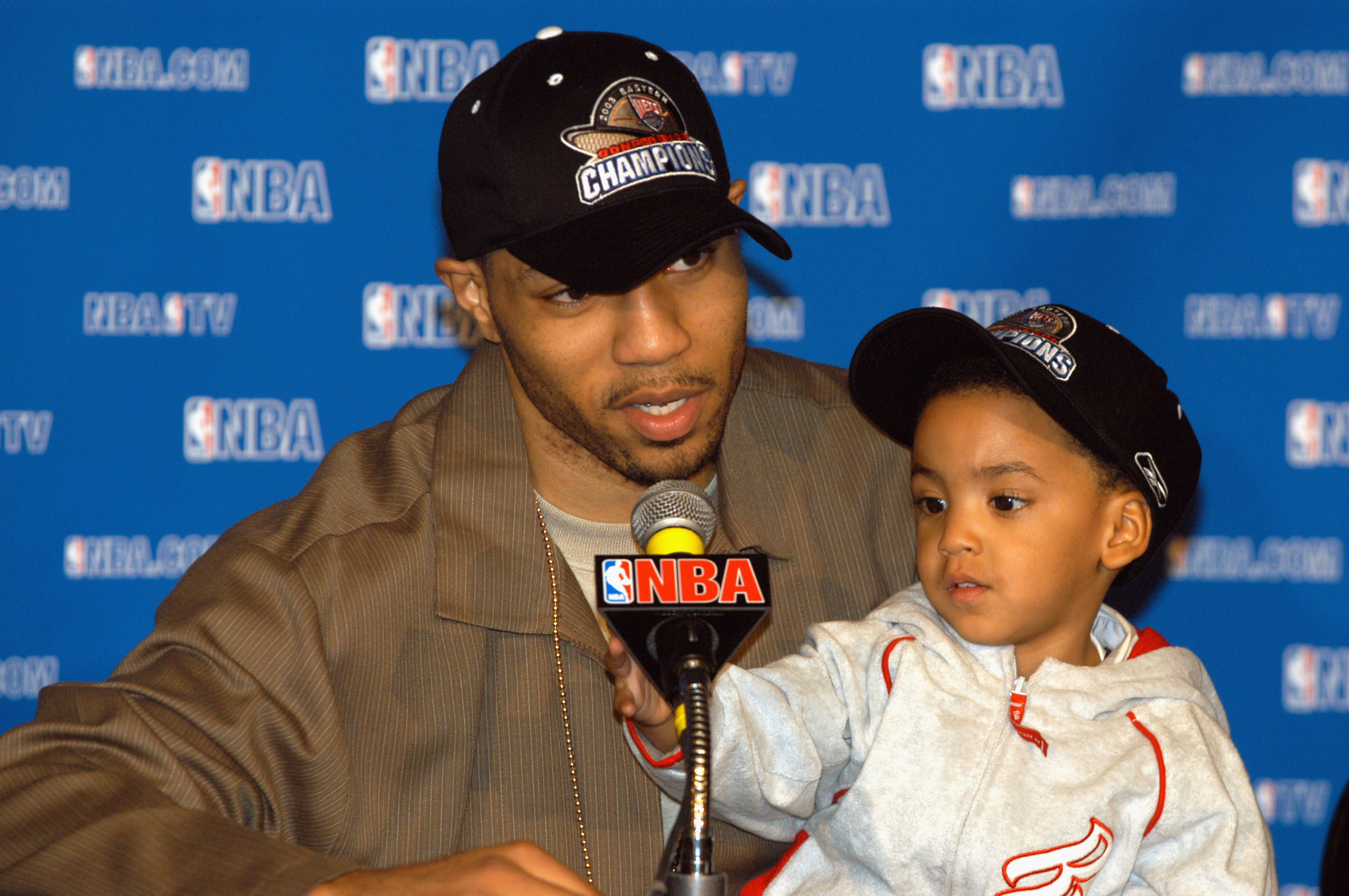 Kenyon Martin #6 of the New Jeresy Nets talks to the press while his son, Kenyon Jr., plays with the microphone after Game four of the Eastern Conference Finals against the Detroit Pistons during the 2003 NBA Playoffs at the Continental Airlines Arena on May 24, 2003 in East Rutherford, New Jersey.