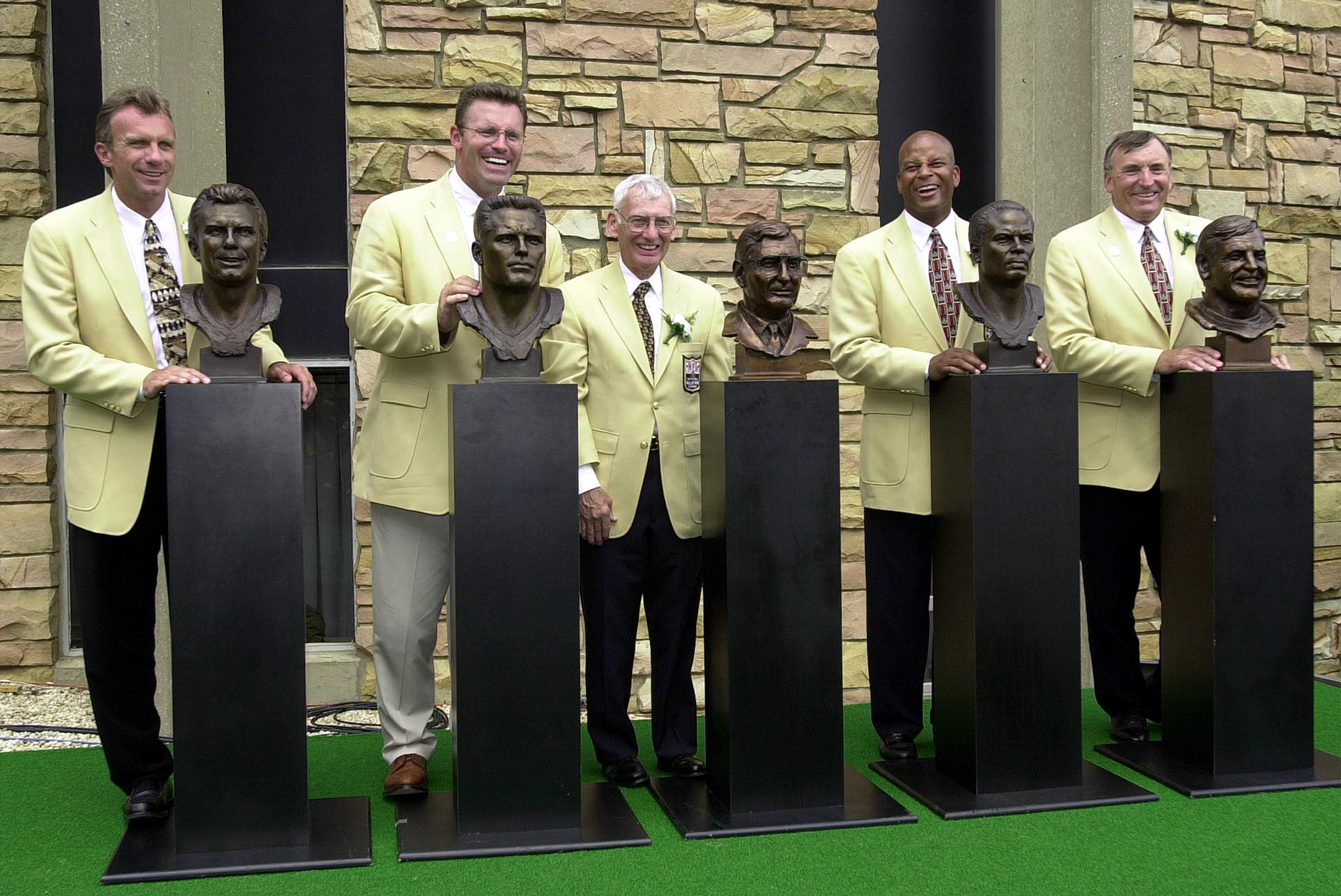 Pro Football Hall of fame enshrinees pose with their busts in front of the Pro Footbal Hall of Fame 29 July 2000 at the Pro Football Hall of Fame in Canton, OH. From left are: Joe Montana, Howie Long, Dan Rooney, Ronnie Lott, and Dave Wilcox.