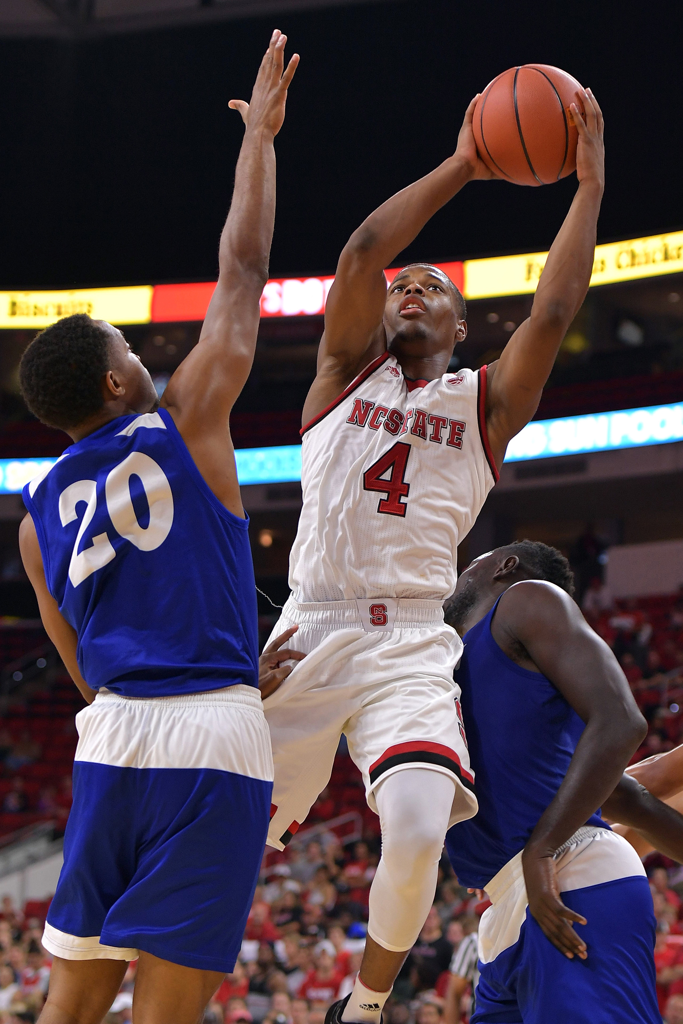 Dennis Smith Jr. #4 of the North Carolina State Wolfpack puts up a shot against Chances Matlock #20 of the Lynn Fighting Knights at PNC Arena on November 3, 2016 in Raleigh, North Carolina.