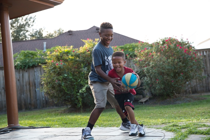 Larry Brooks of the Beaumont Bulls senior youth football team plays basketball with his brothers and sister in his back yard in Beaumont, Texas.