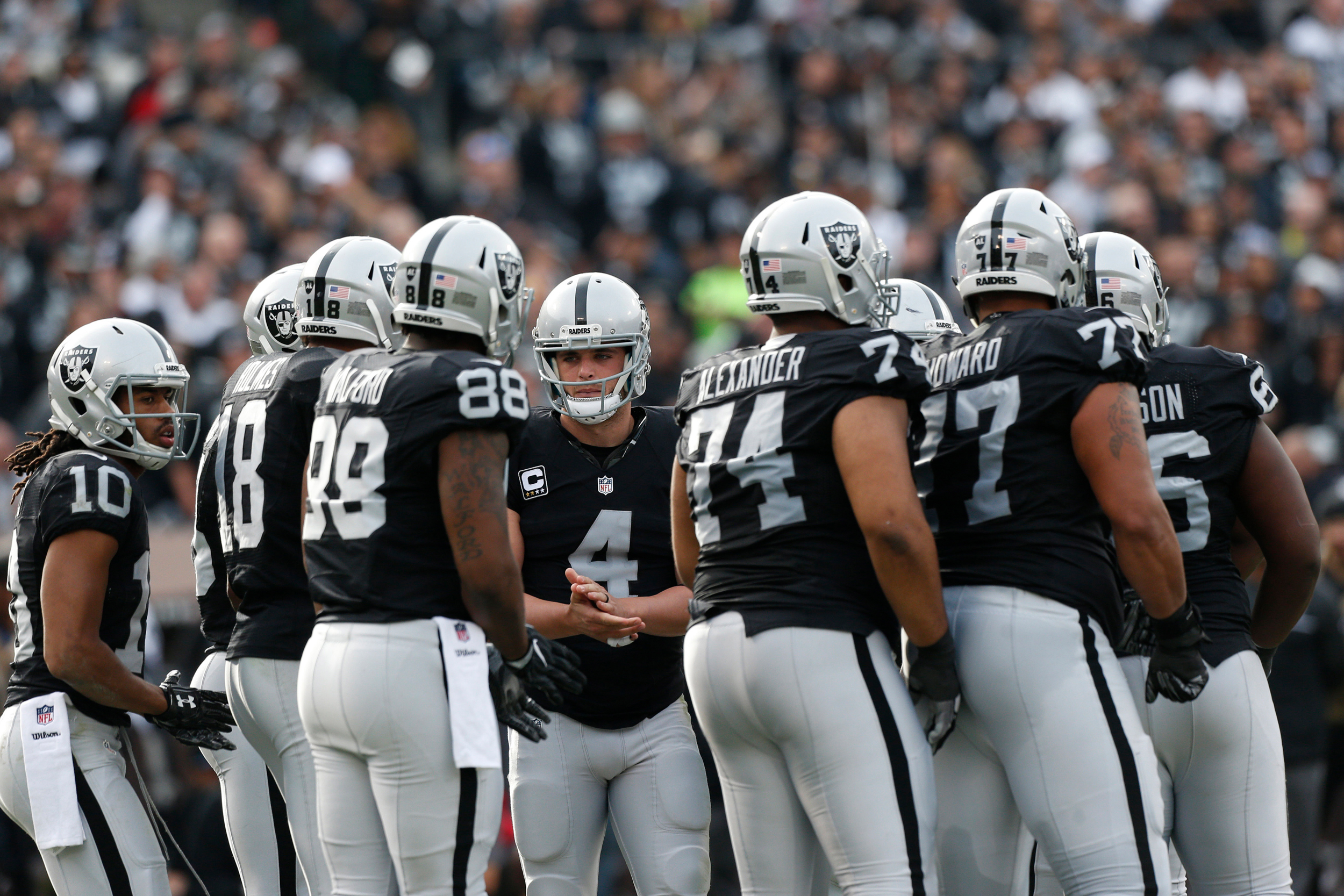 Oakland Raiders quarterback Derek Carr (4) stands in the team huddle against the Buffalo Bills in the second quarter at Oakland Coliseum.