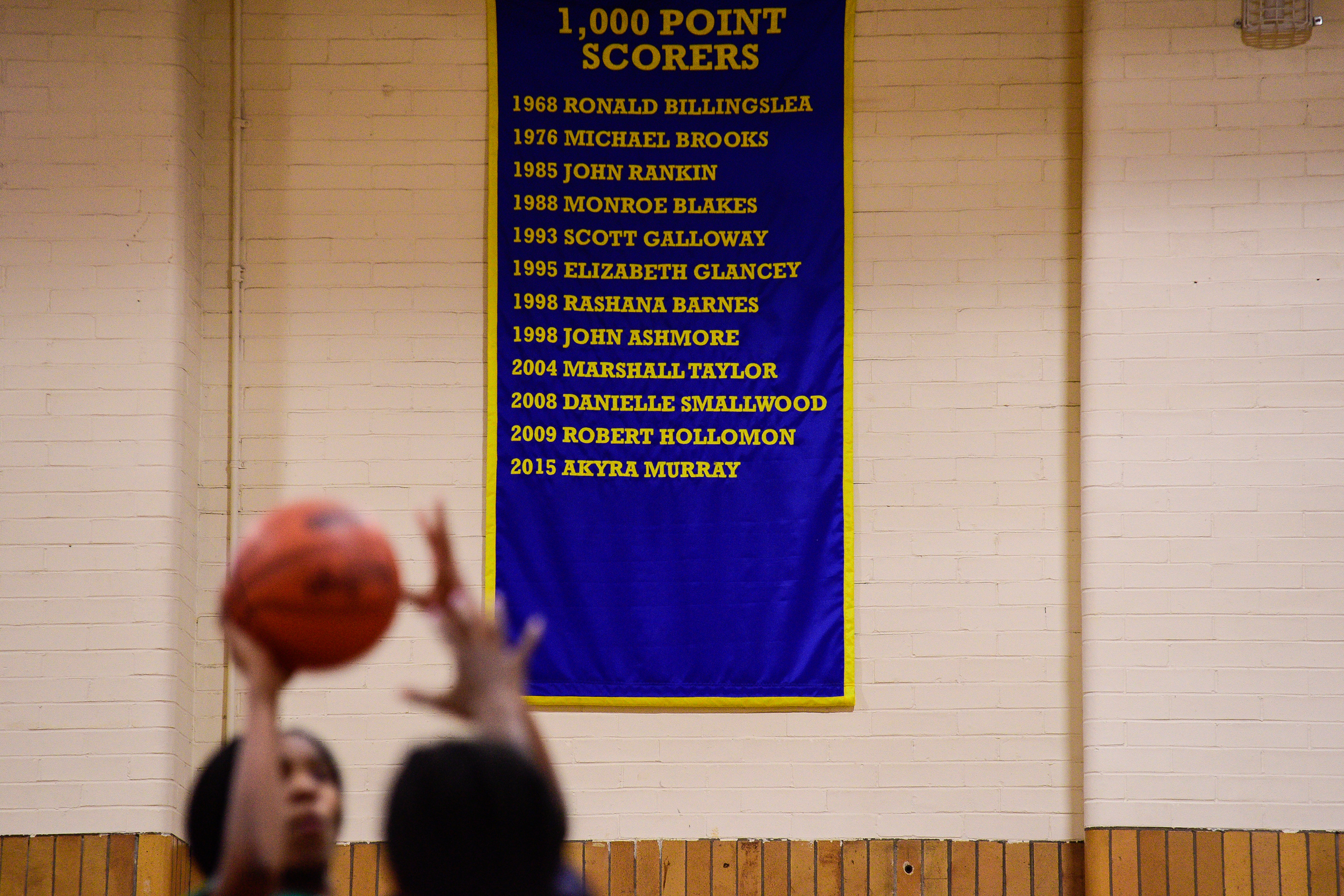 A banner highlighting 1,000 point scorers hangs on the wall of the gym during girls basketball practice at West Catholic High School.