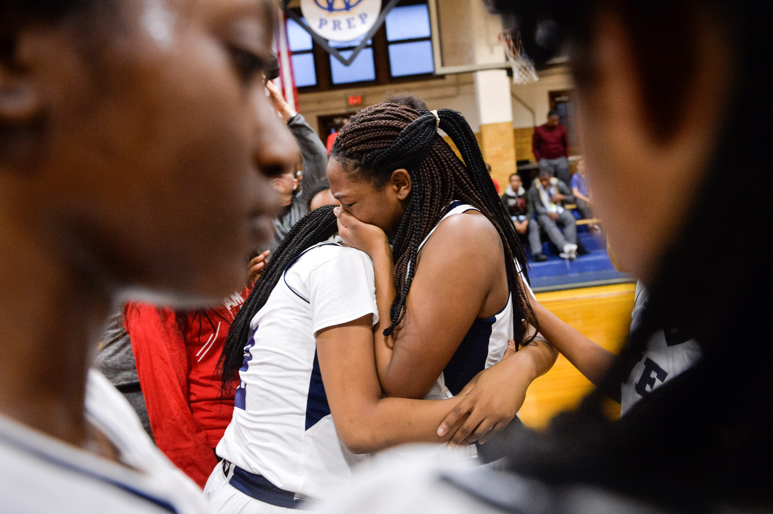 West Catholic girls basketball player Morgan Kennedy cries and is hugged by a teammate after a ceremony to honor Akyra Murray during the team's first home game. Pulse nightclub shooting victim Akyra Murray graduated from West Catholic just days before she was killed, and led her team to two district championships and scored over 1,000 points during her career at the school.