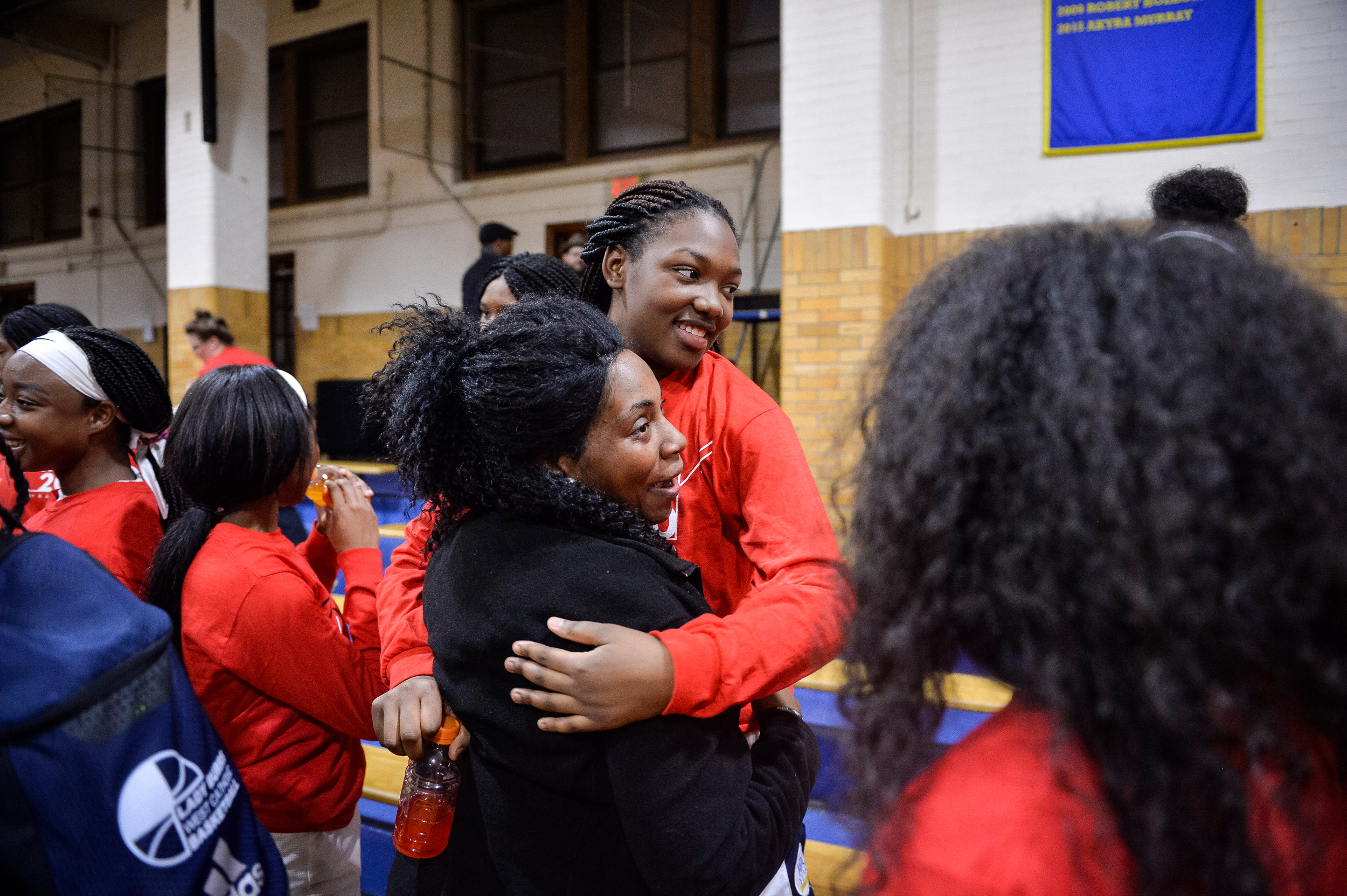 Senior Morgan Kennedy hugs Akyra Murray's mother Natalie after the first home girls basketball game at West Catholic High School.
