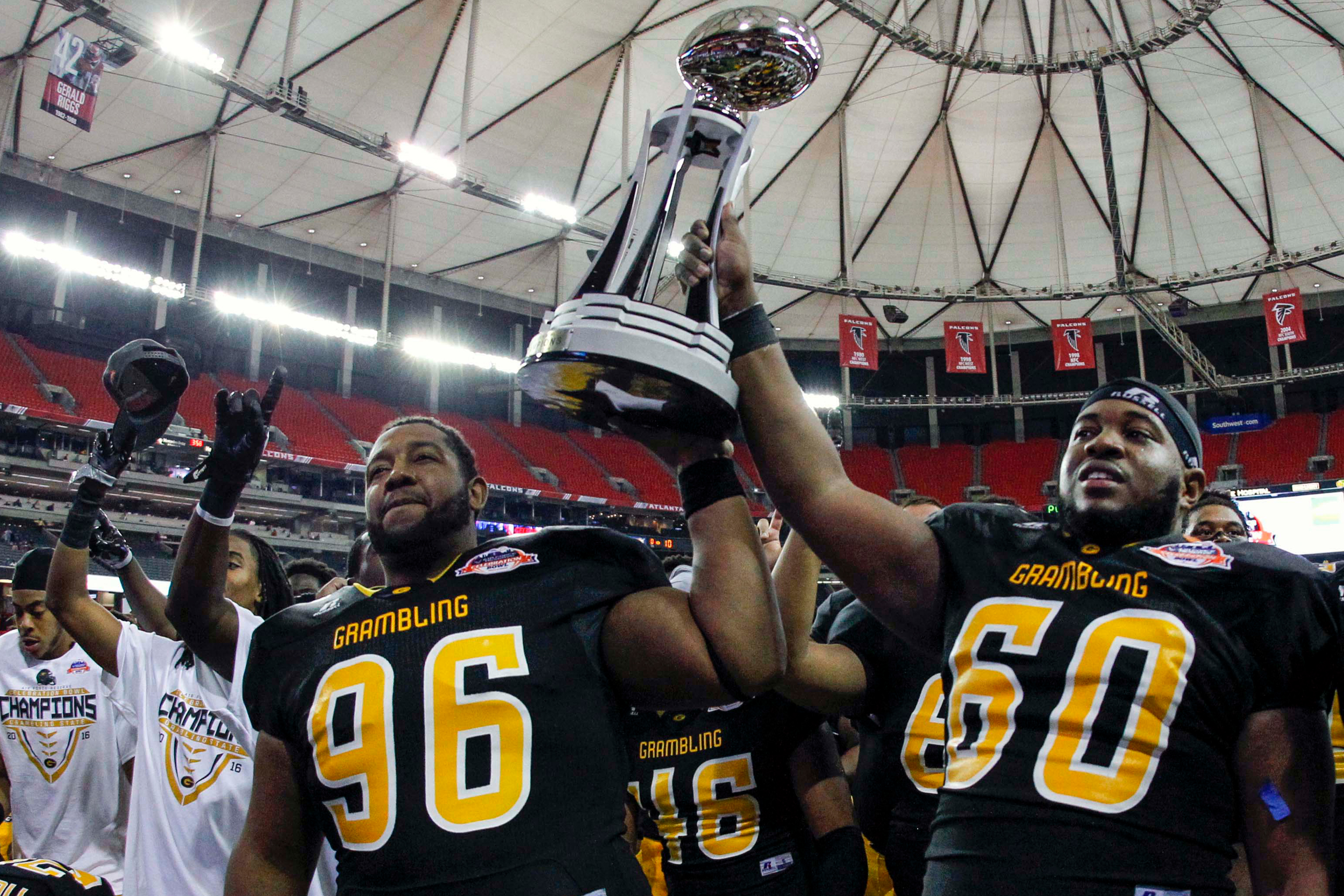 Grambling State Tigers defensive lineman DeVaughn Madise (96) and offensive lineman Terry Boyd (60) lift the trophy after a victory against the North Carolina Central Eagles in the Celebration Bowl at the Georgia Dome. Grambling State won 10-9.