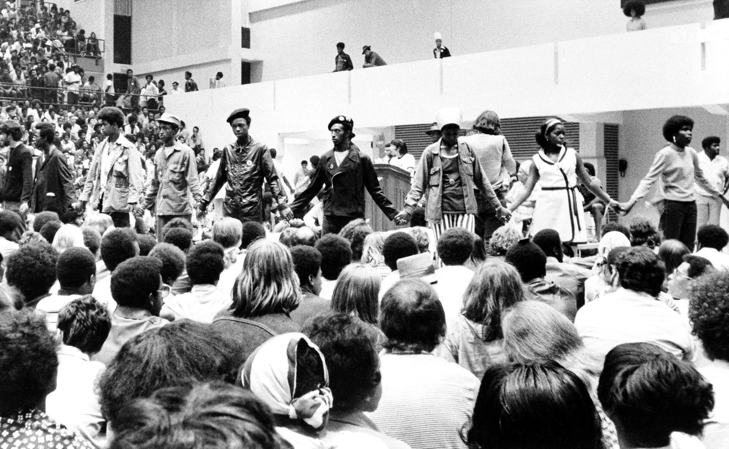 Security guard hold hands as they form a circle around the speakers platform during the Black Panthers conference in Philadelphia, Sept. 7, 1970. A crowd of about 6,000 persons filled McGonigle Hall, a gymnasium at Temple University to listen to the speeches.