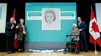 Canada's Finance Minister Bill Morneau stands with Wanda Robson after her sister Viola Desmond was chosen to be featured on a new $10 bank note during a ceremony at the Museum of History in Gatineau
