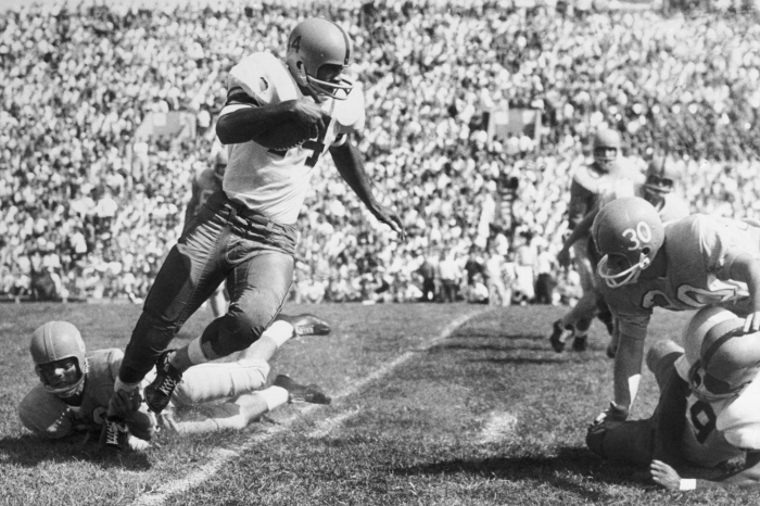 Syracuse runnerback Ernie Davis picks up six yards against Kansas around his right end before being run out of bounds.