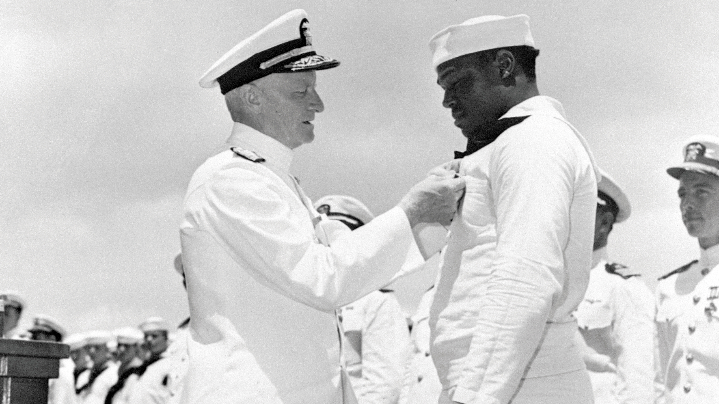 Admiral Chester W. Nimitz pins the Navy Cross on Dorie Miller, the first African-American to win the award, in ceremony aboard a warship at Pearl Harbor.
