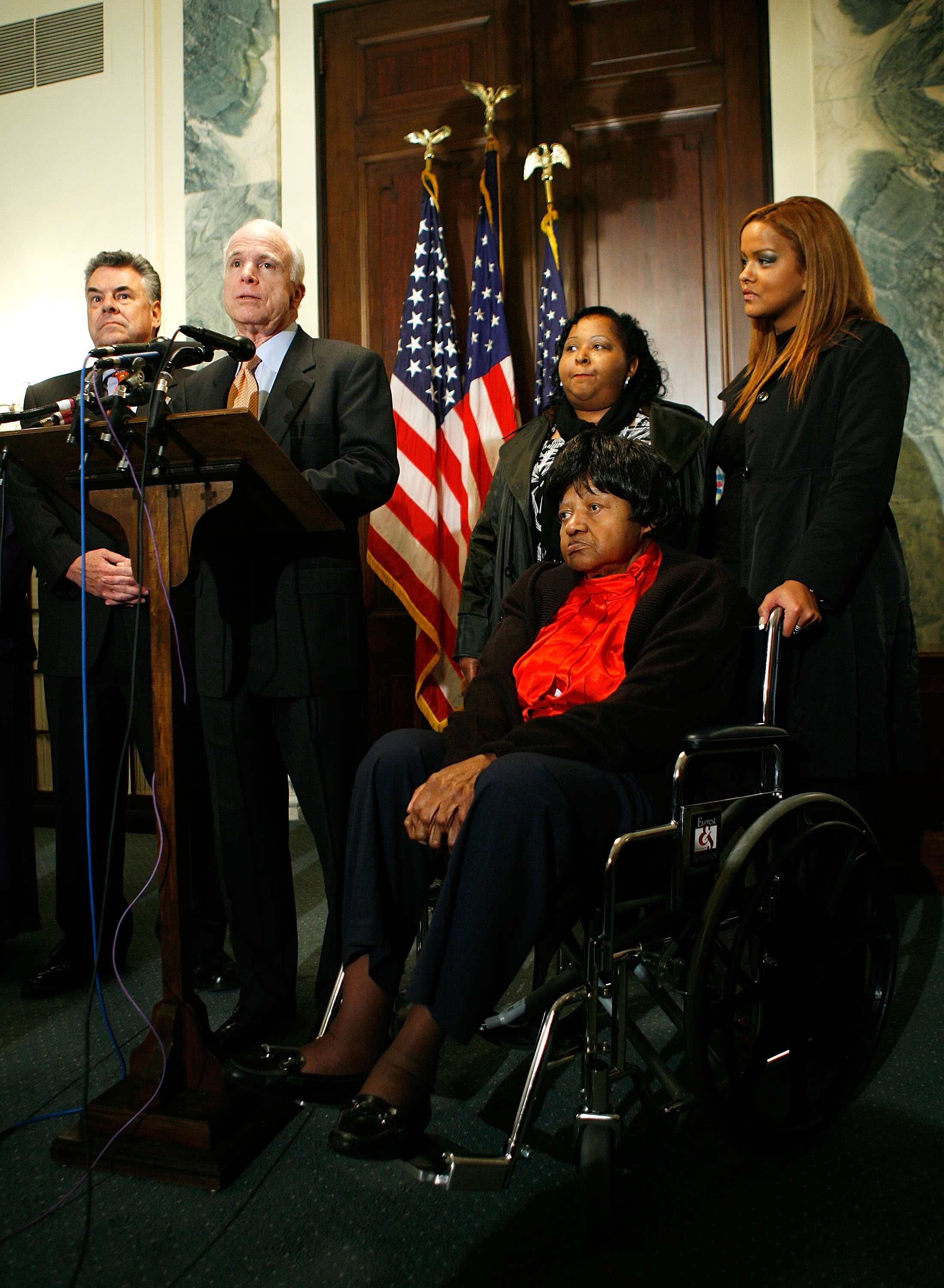 "U.S. Sen. John McCain (R-AZ) (2L) speaks as Dorothy Cross (2R, in wheelchair), great niece of the first African American heavyweight boxing champion John Arthur ""Jack"" Johnson, Cross's daughter Constance Hines (C), Cross's family friend Betsy Victoria (R), and Rep. Peter King (R-NY) (L) listen during a news conference on Capitol Hill April 1, 2009 in Washington, DC. Sen. McCain and Rep. Peter King (R-NY) introduced a resolution calling on President Barack Obama to posthumously pardon Johnson, who was a victim of what is widely regarded as a racially motivated conviction in 1913 for violating a law prohibiting taking women across state lines for ""immoral purposes""."