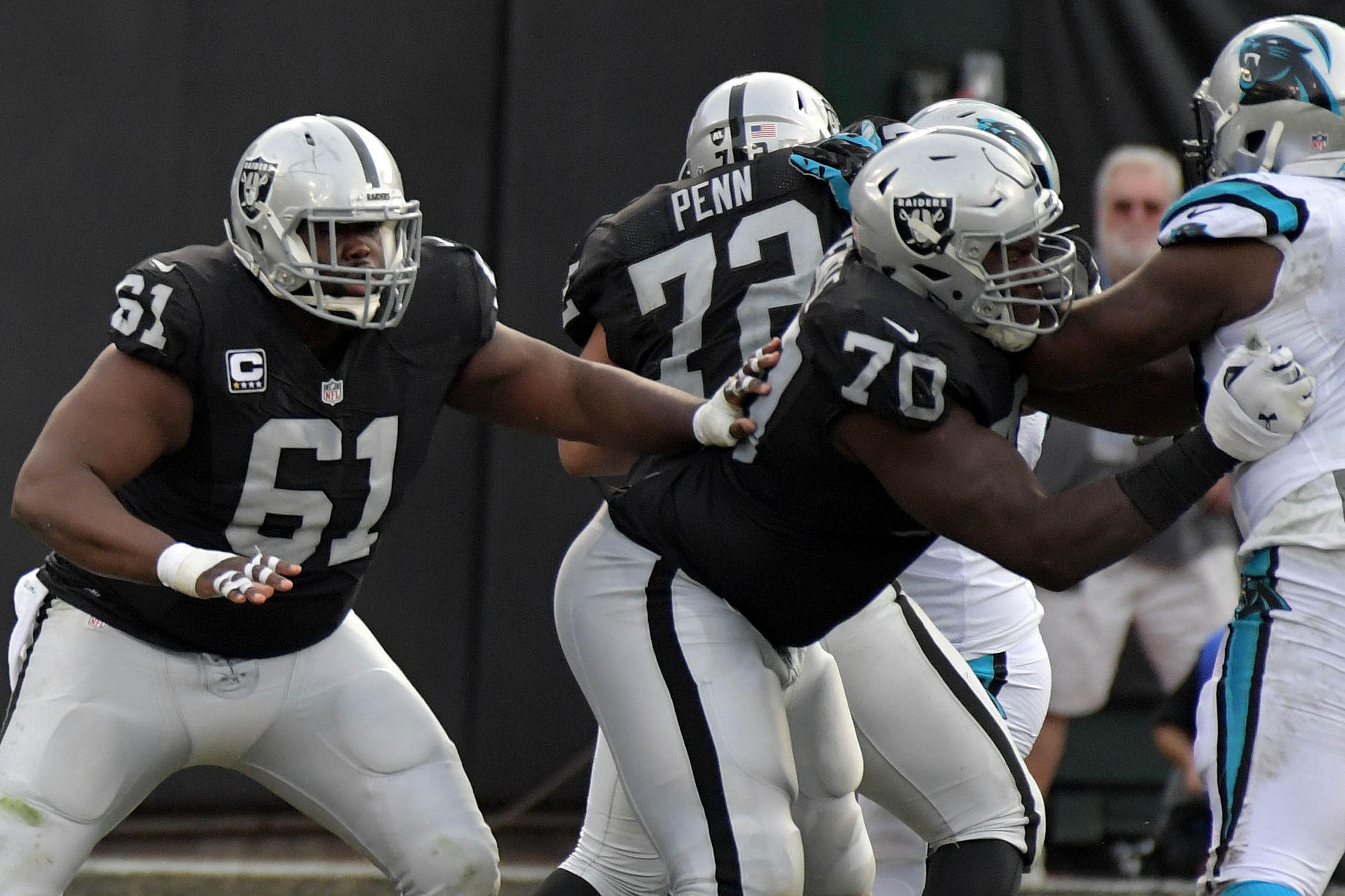 Oakland Raiders quarterback Derek Carr (4) throws as center Rodney Hudson (61) and offensive guard Kelechi Osemele (70) block against the Carolina Panthers during the second half at Oakland-Alameda County Coliseum.