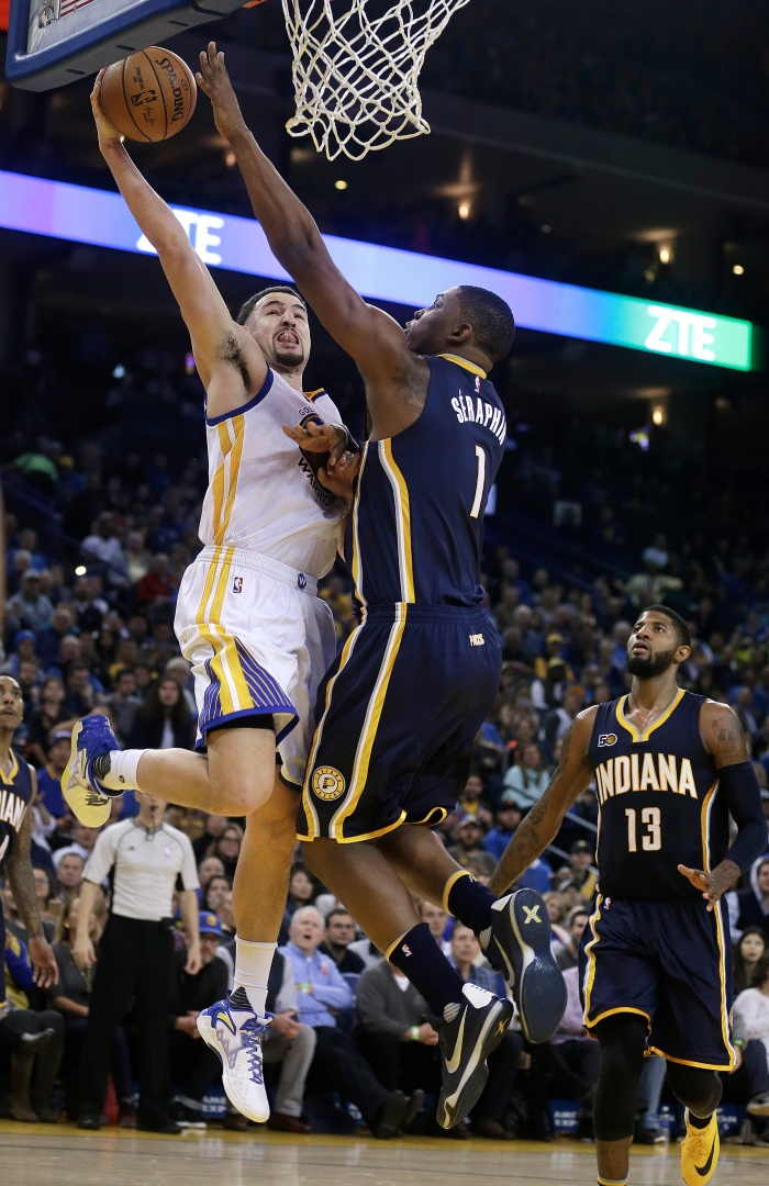 Golden State Warriors' Klay Thompson, left, lays up a shot against Indiana Pacers' Kevin Seraphin (1) during the third quarter of an NBA basketball game Monday, Dec. 5, 2016, in Oakland, Calif.