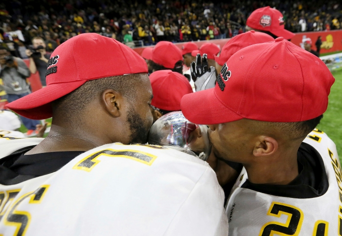 Grambling State's Trent Scott, left, and Tyler Oliver kiss the Southwestern Athletic Conference championship trophy after defeating Alcorn State in the NCAA college football game Saturday, Dec. 3, 2016, in Houston.