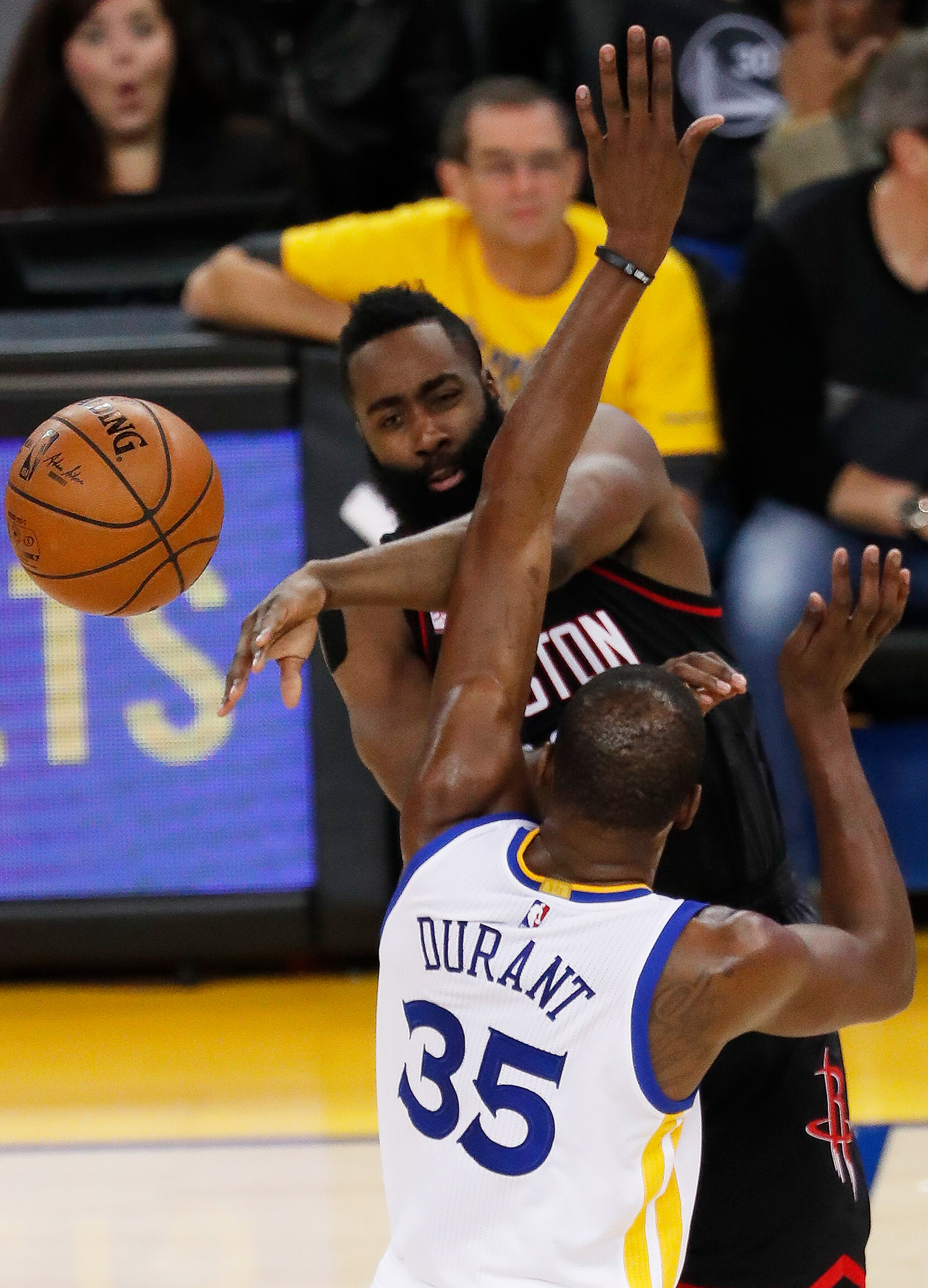 Houston Rockets guard James Harden (top) passes as Golden State Warriors forward Kevin Durant (bottom) defends during the first half of the NBA basketball game between the Houston Rockets and the Golden State Warriors at the Oracle Arena in Oakland, California, December 1, 2016.