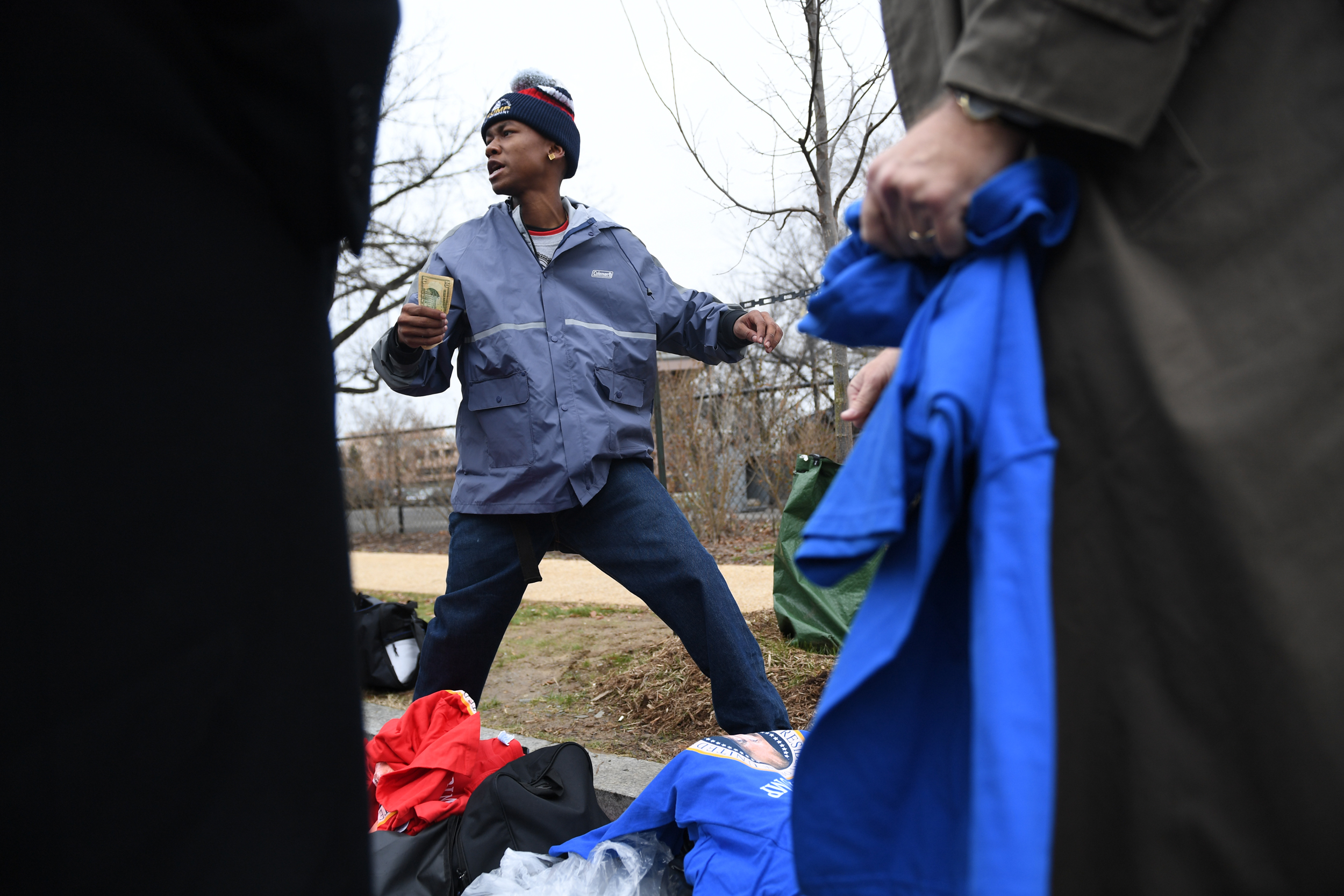 A young vendor makes t-shirts and hat sales to people as they make their way from the National Mall on January 20, 2017: during the inauguration of President Donald Trump January 20, 2017 on the National Mall in Washington D.C. . (Brent Lewis/The Undefeated)