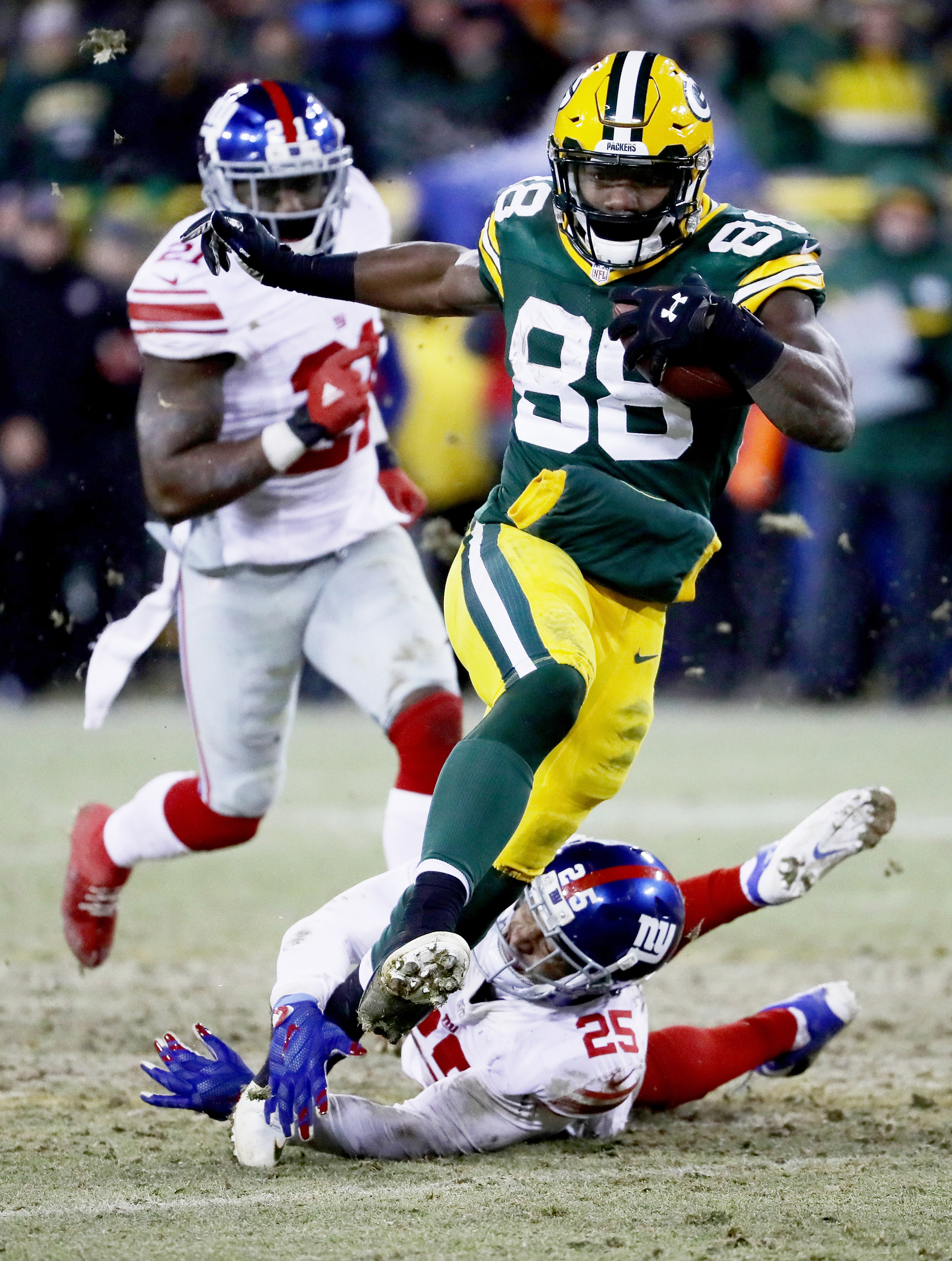 Ty Montgomery #88 of the Green Bay Packers escapes a tackle attempt by Leon Hall #25 of the New York Giants in the fourth quarter during the NFC Wild Card game at Lambeau Field on January 8, 2017 in Green Bay, Wisconsin.