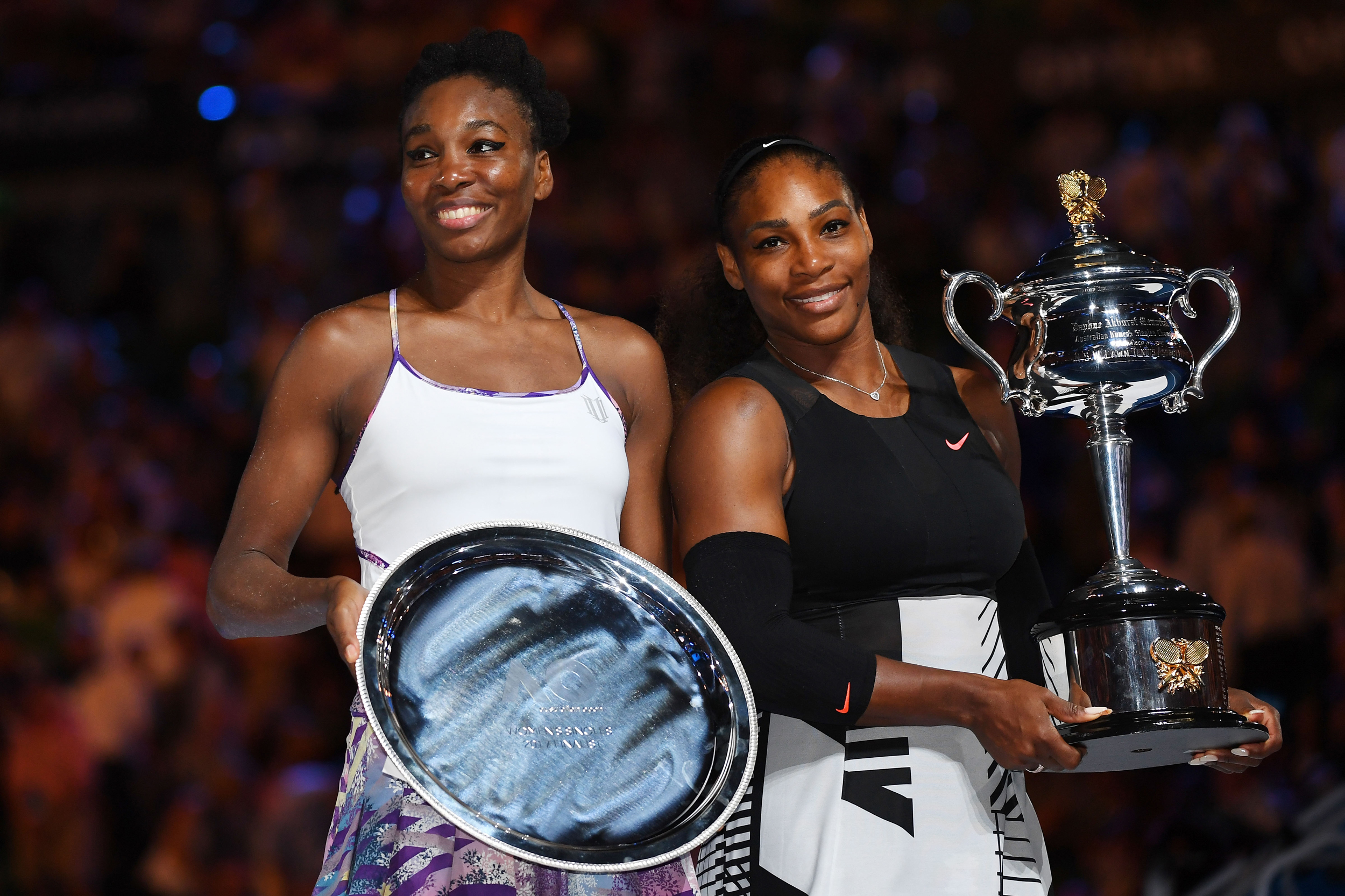 Serena Williams of the United States poses with the Daphne Akhurst Trophy alongside Venus Williams of the United States after the Women's Singles Final on day 13 of the 2017 Australian Open at Melbourne Park on January 28, 2017 in Melbourne, Australia.