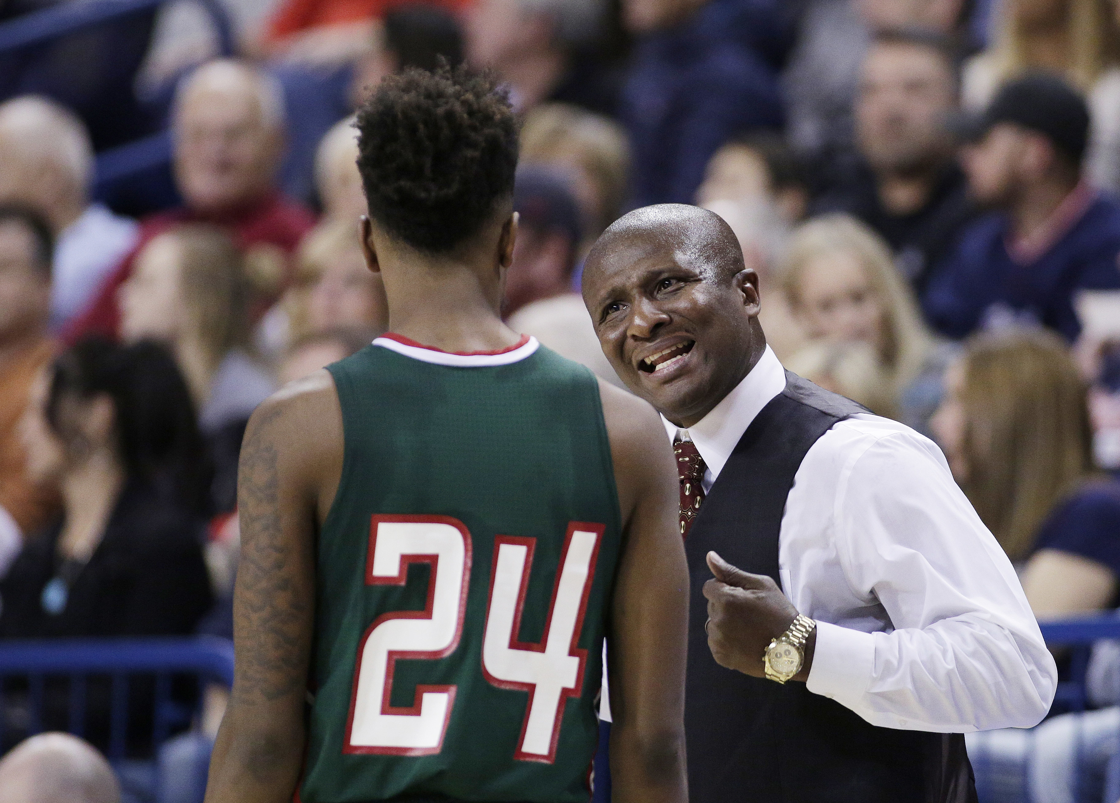 Mississippi Valley State coach Andre Payne, right, speaks with guard Isaac Williams (24) during the team's NCAA college basketball game against Gonzaga in Spokane, Wash. MVSU and Texas Southern are among a handful of lower-level Division I teams that lead a nomadic existence during non-conference play, traveling to play road games with guaranteed payouts.