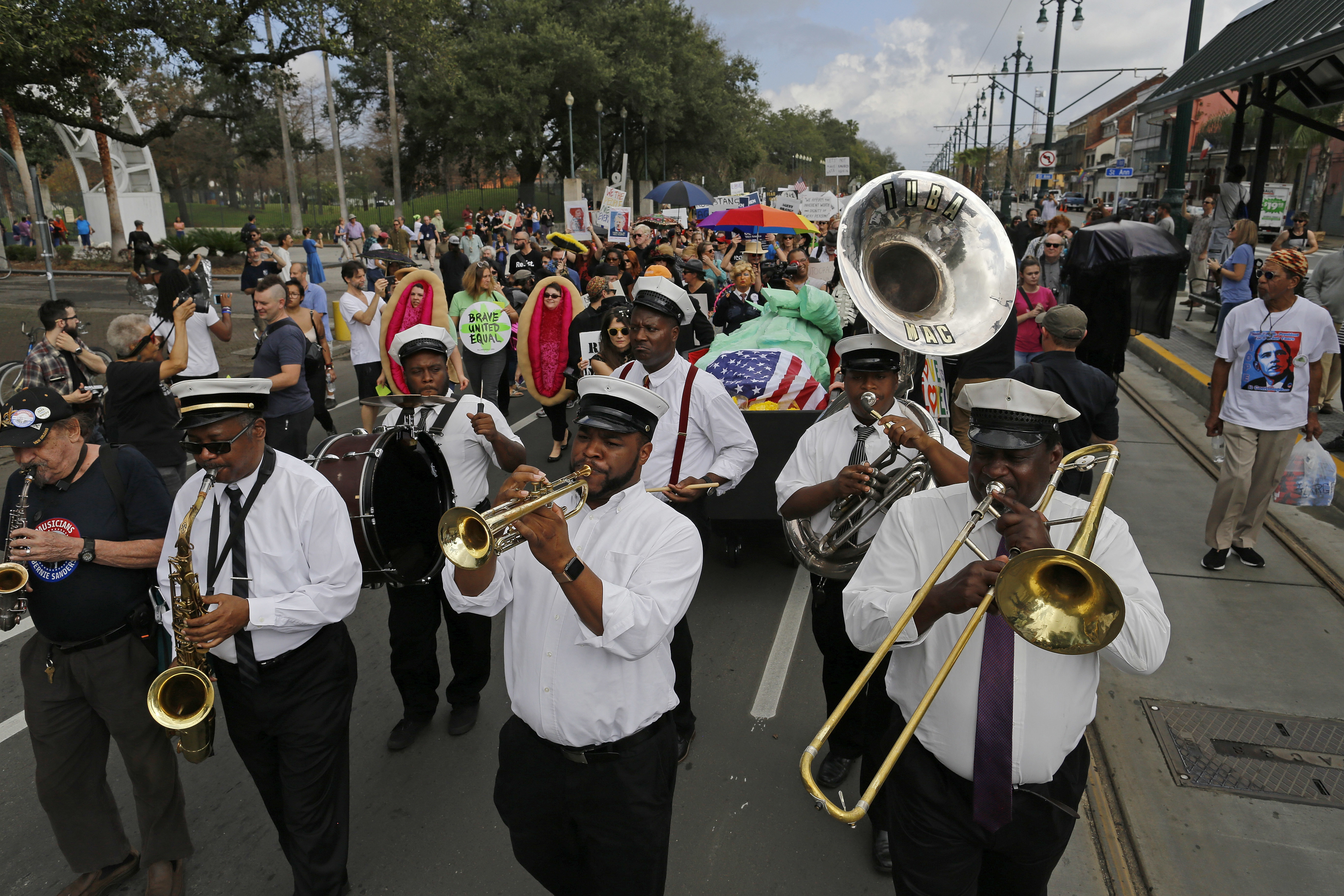 Members of the Mahogany Brass Band lead a mock second line jazz funeral procession down the streets of New Orleans in protest of the inauguration of Donald Trump Friday, Jan. 20, 2017. (AP Photo/Max Becherer)