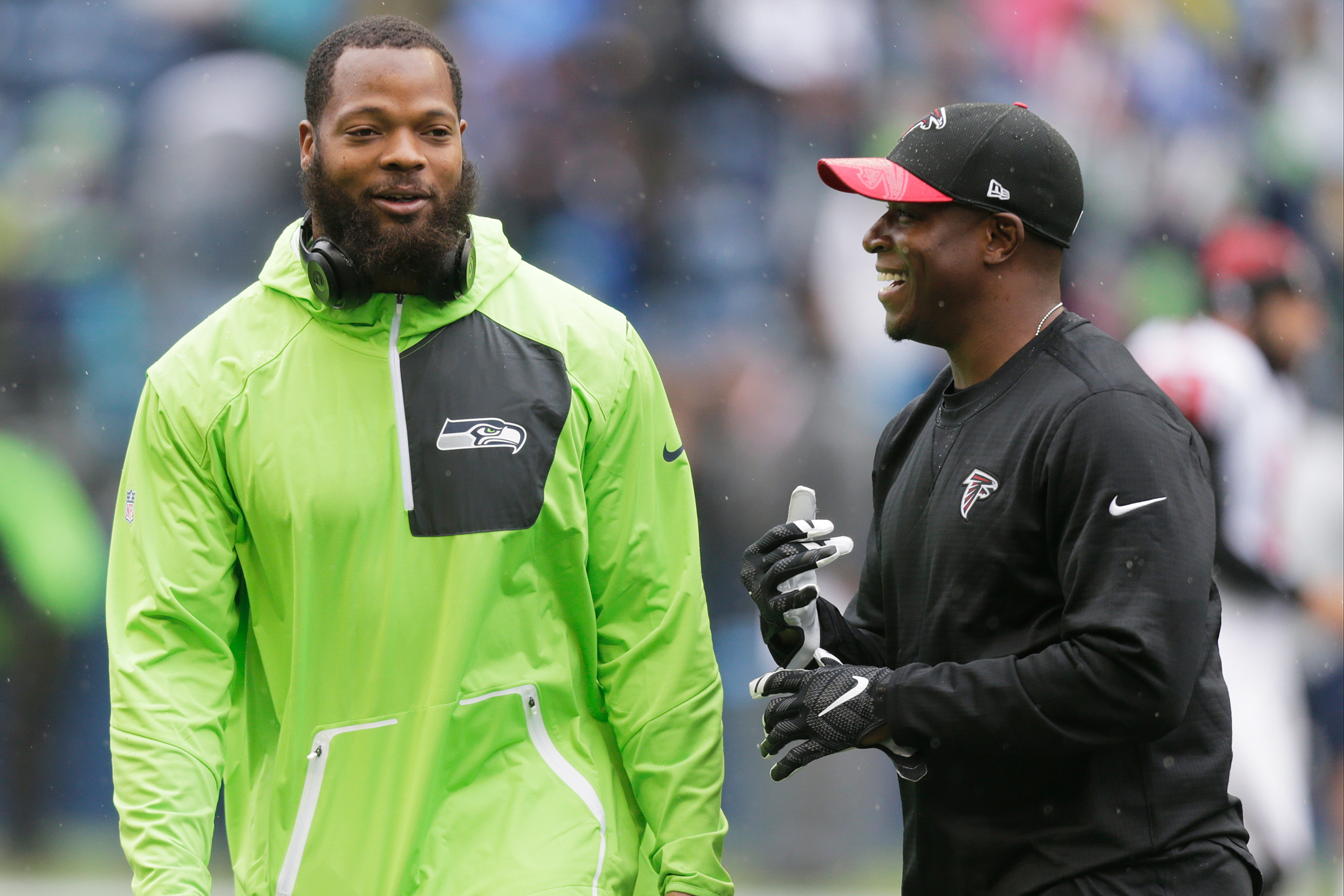 Seattle Seahawks defensive end Michael Bennett, left, talks with Raheem Morris, Atlanta Falcons assistant head coach and and wide receivers coach, before an NFL football game, Sunday, Oct. 16, 2016, in Seattle.