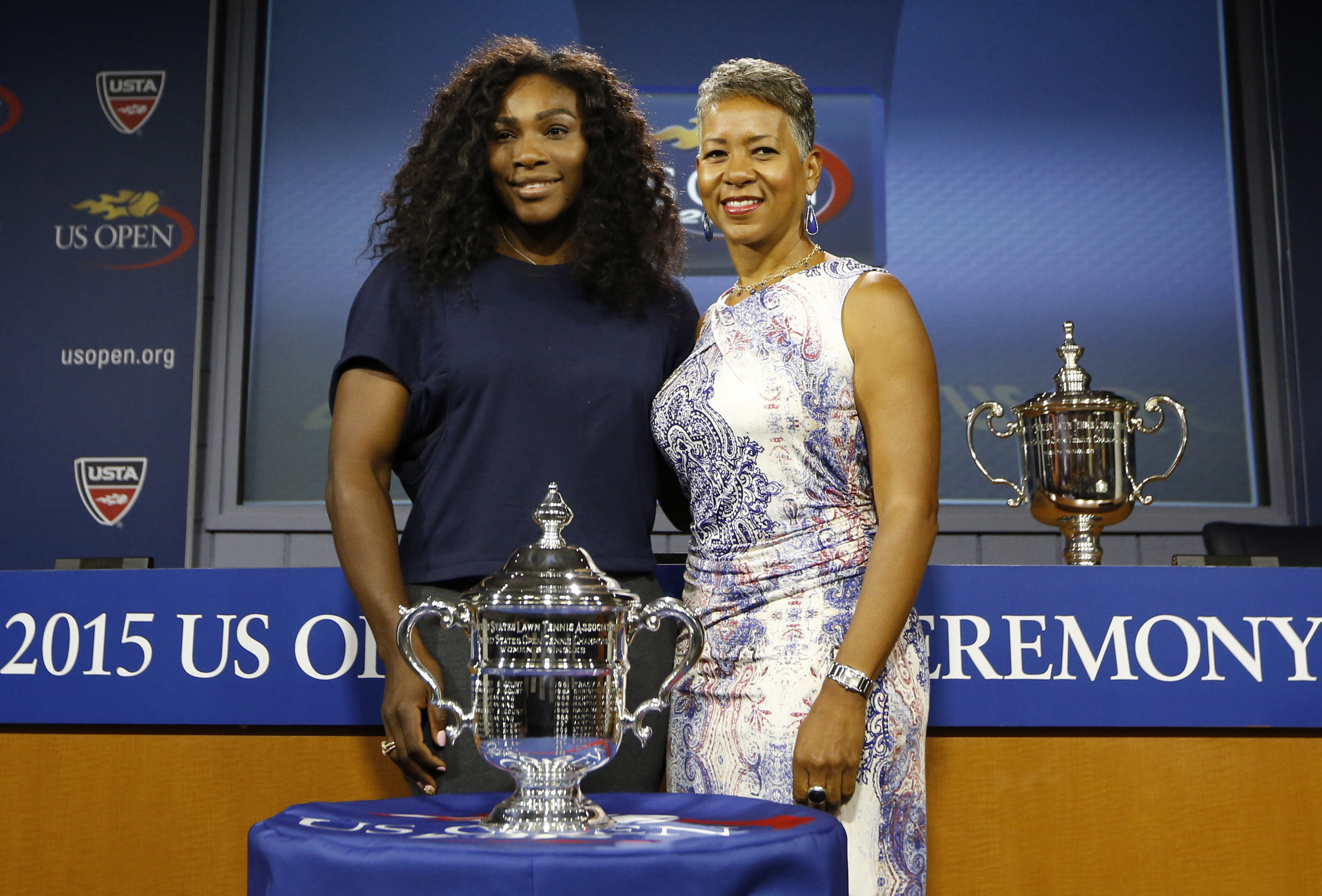Defending U.S. Open Tennis women's singles champion Serena Williams, left, of the United States, poses with USTA president Katrina Adams and the women's singles trophy following a news conference and the U.S. Open draw ceremony at the USTA Billie Jean King National Tennis Center in New York, Thursday, Aug. 27, 2015.