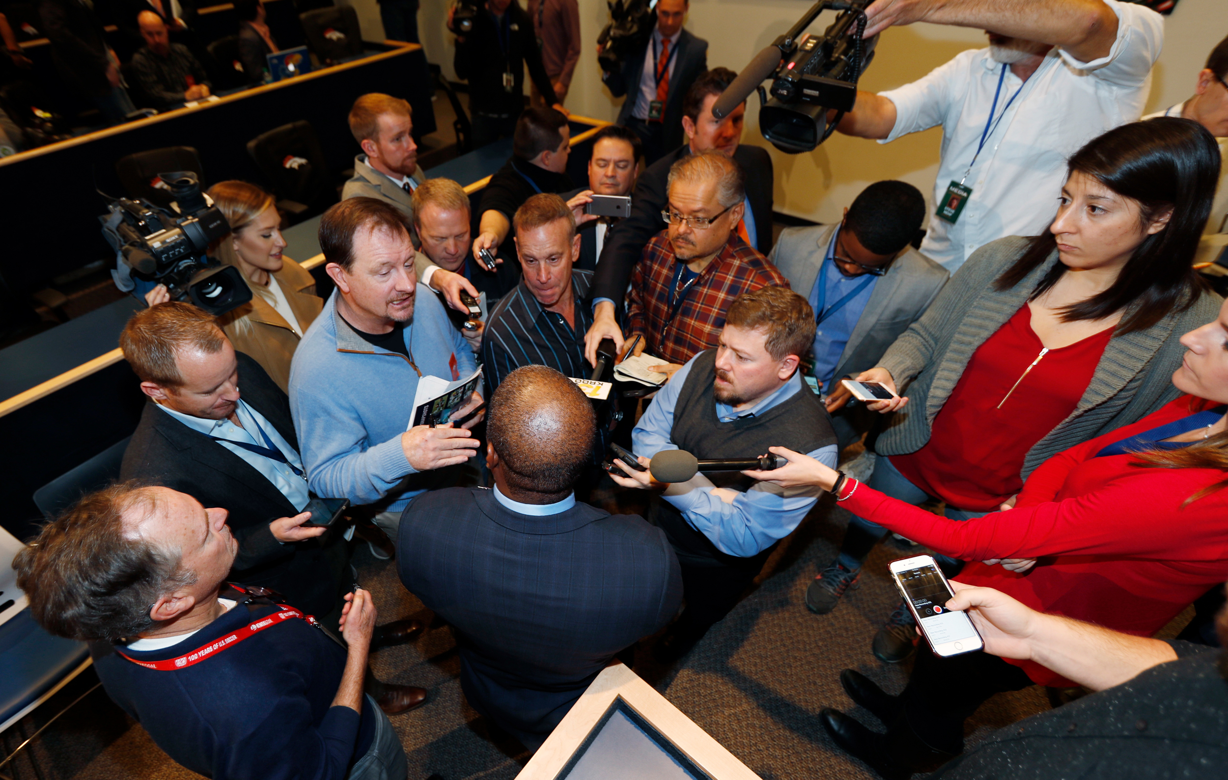 Vance Joseph, bottom center, is surrounded by reporters after Joseph was introduced as the new head coach of the Denver Broncos during a news conference at the team's headquarters Thursday, Jan. 12, 2017, in Englewood, Colo.