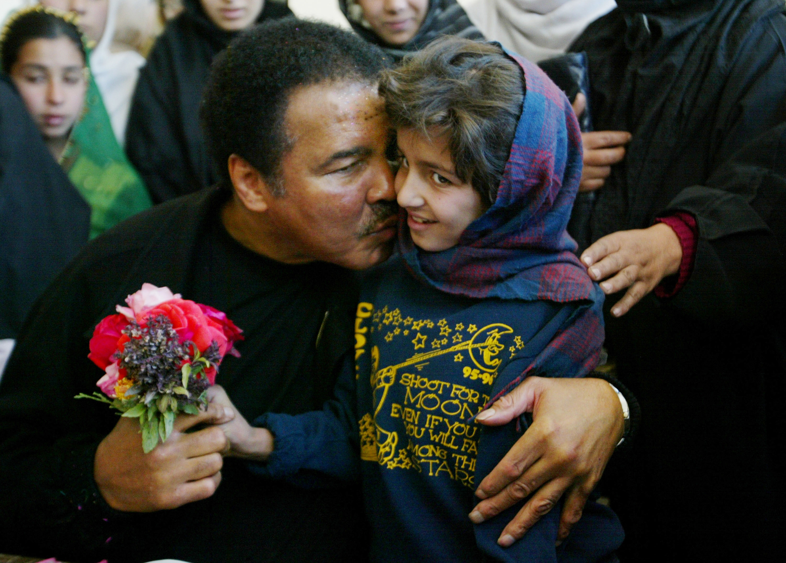 "Former world heavyweight boxing champion Muhammad Ali (L) gives a kiss to a Afghan students during his visit to Karte Sei High school for Girls November18, 2002 in Kabul, Afghanistan. Ali is in Kabul on a three-day mission as a special UN guest as the ""U.N. Messenger of Peace."""
