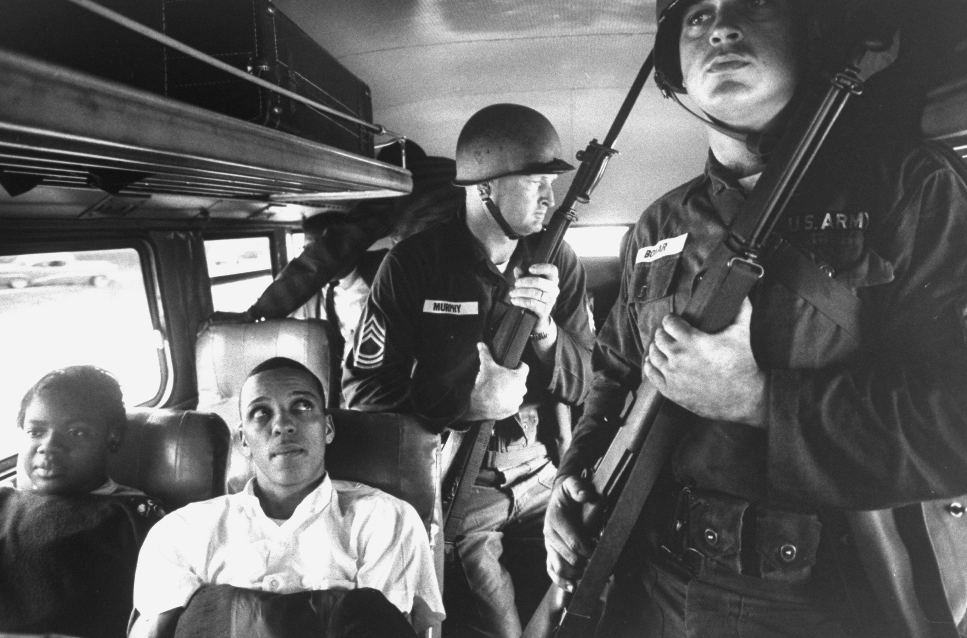 (L-R) Freedom Riders Julia Aaron & David Dennis sitting on board interstate bus as they & 25 others (bkgrd. & unseen) are escorted by 2 MS Natl. Guardsmen holding bayonets, on way fr. Montgomery, AL to Jackson, MS.