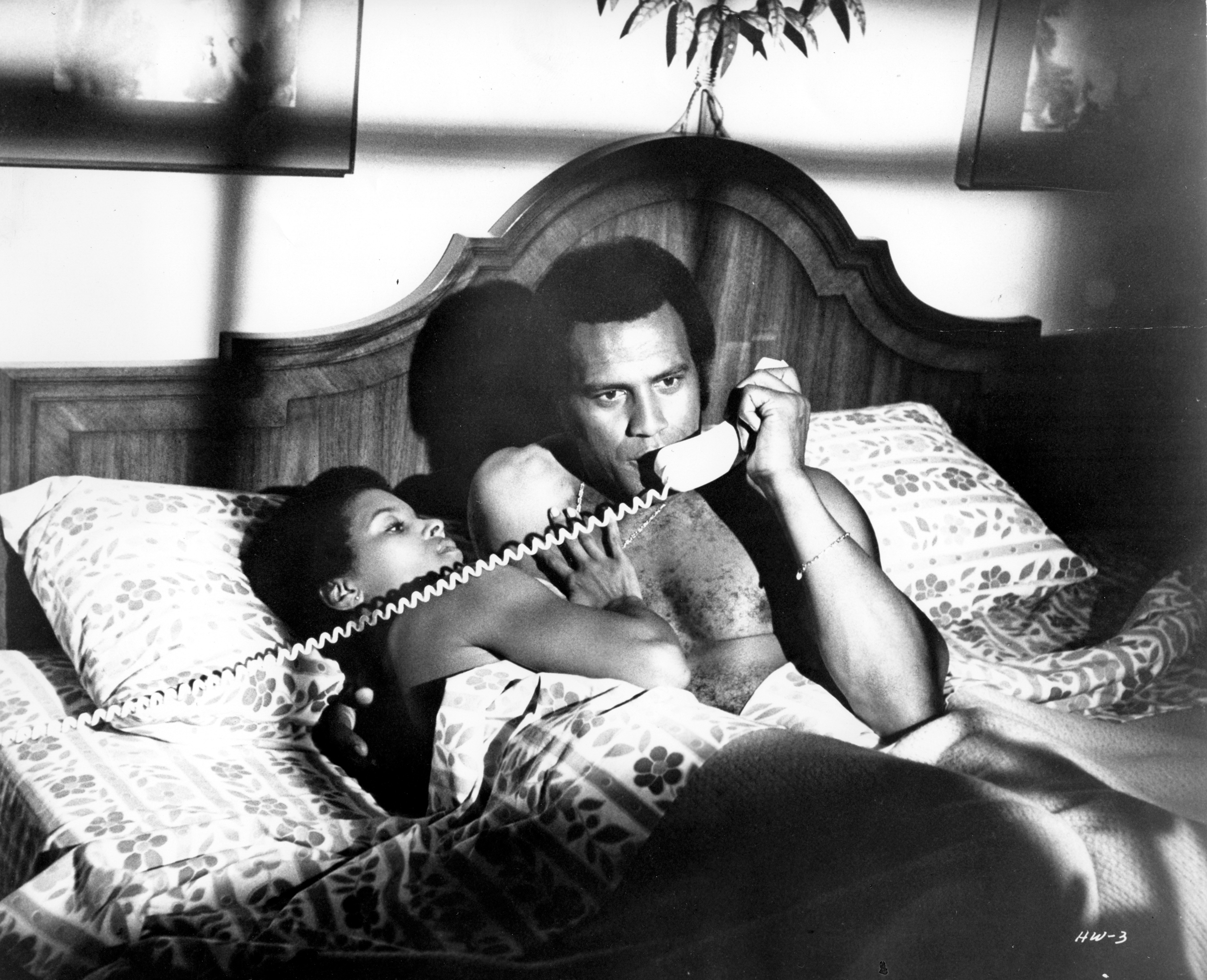 "Fred Williamson as Jagger Daniels receives an emergency phone call as girl friend Jeannie Bell looks on in a scene from the movie""Three the Hard Way"" , circa 1974."