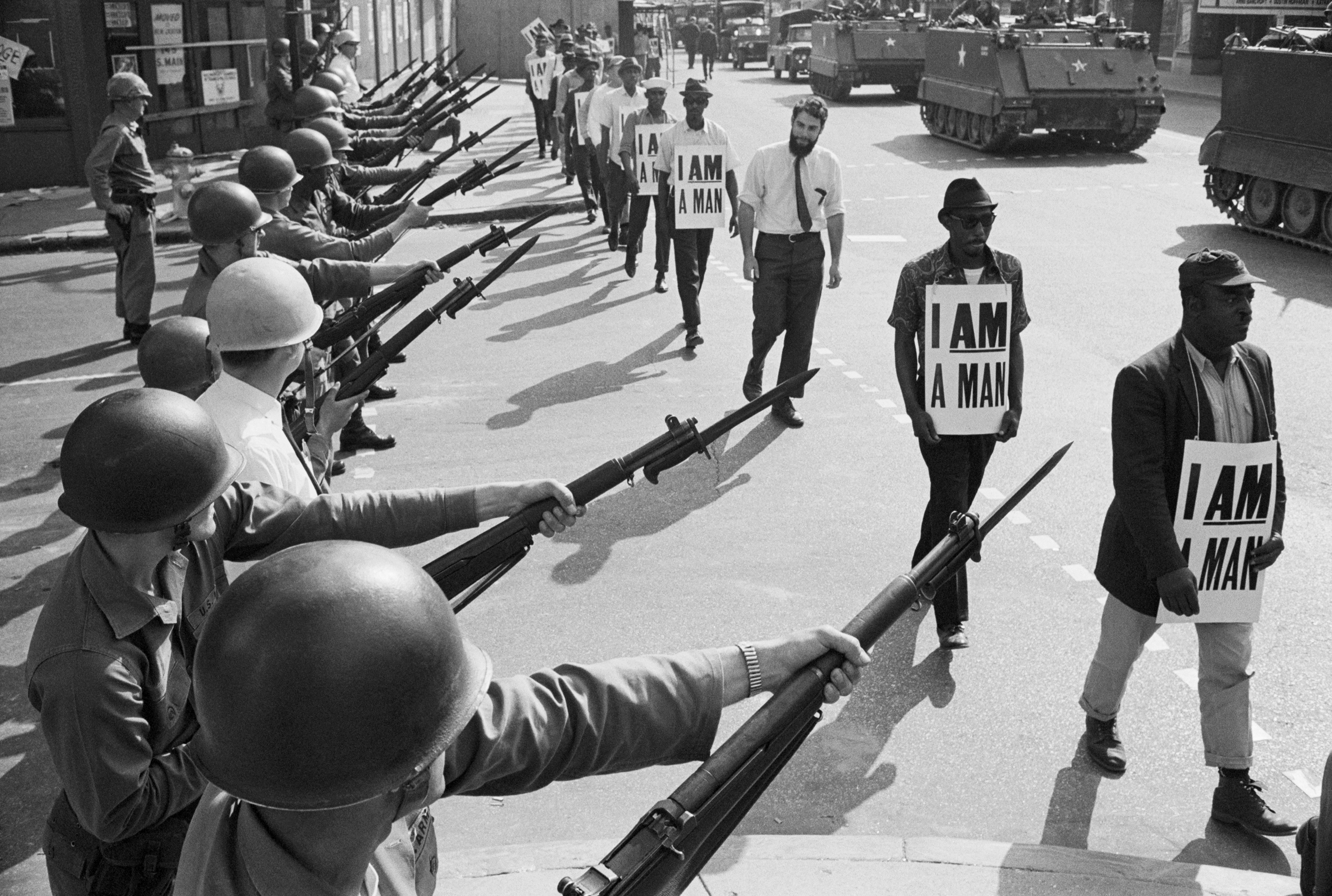 "U.S. National Guard troops block off Beale Street as Civil Rights marchers wearing placards reading, ""I AM A MAN"" pass by on March 29, 1968. It was the third consecutive march held by the group in as many days. Rev. Martin Luther King, Jr., who had left town after the first march, would soon return and be assassinated."