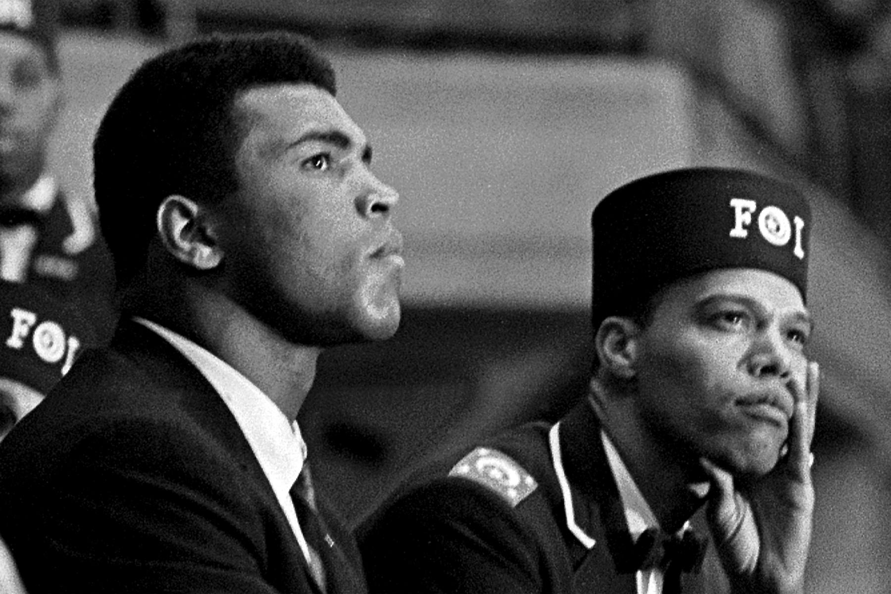 Close-up of American boxer Muhammad Ali (born Cassius Clay) (left) and Nation of Islam leader Louis Farrakhan (born Louis Walcott) as they listen to a speaker during the Saviour's Day celebrations at the International Ampitheatre, Chicago, Illinois, February 27, 1966. Farrakhan wears a Fruit of Islam uniform, a subset of the Nation of Islam.