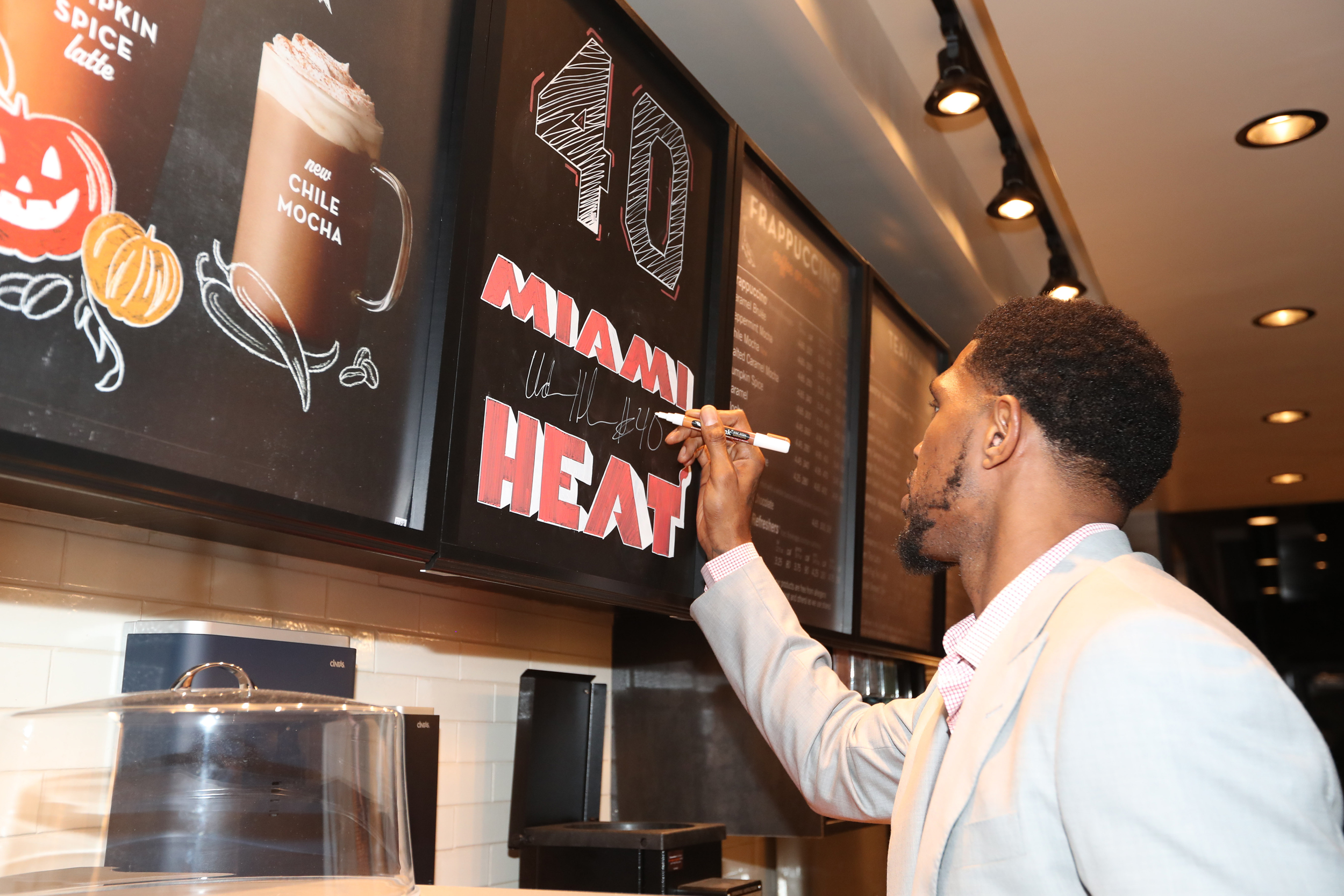Miami Heat's Udonis Haslem signs autograph on the wall behind the Starbucks counter at the VIP preview of Starbucks hosted by Udonis Haslem and Ramona Hall at Jackson Memorial Medical Center on October 24, 2016 in Miami, FL.