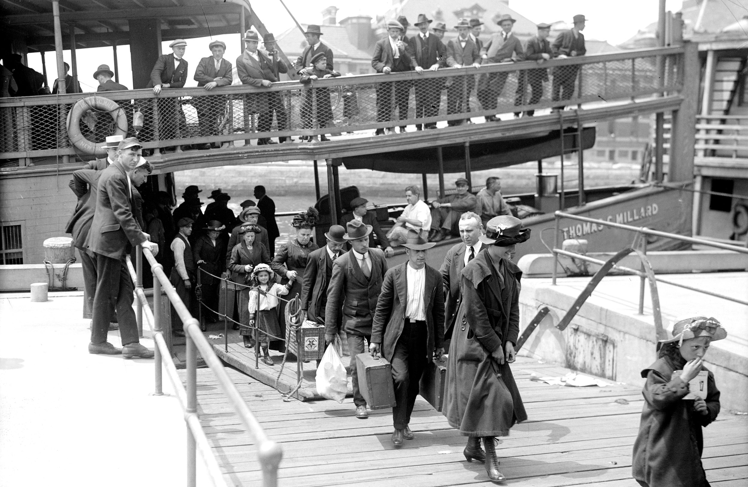 Newly arrived immigrants disembark from the passenger steamer Thomas C. Millard upon their arrival at Ellis Island, in New York, early twentieth century.