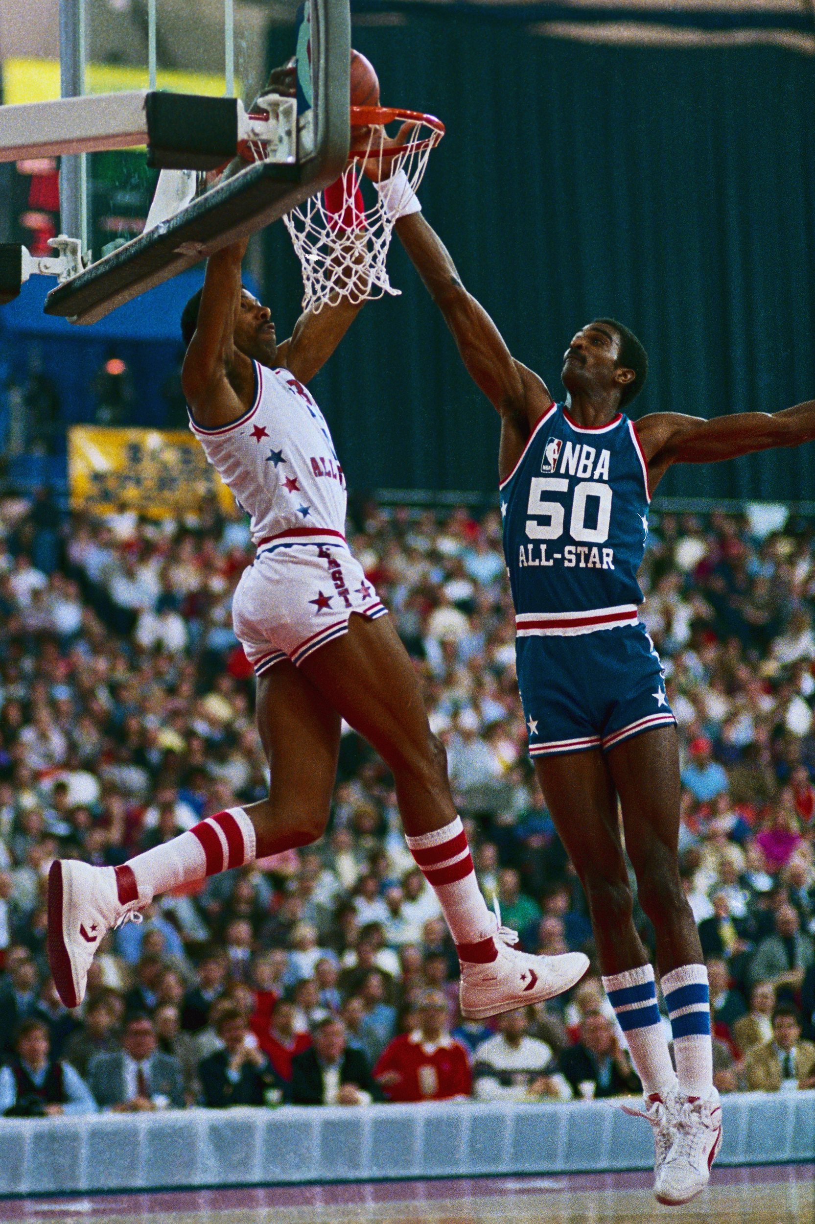 NBA Eastern Conference All Star drives for layup past defender Western Conference's Ralph Sampson (50) in first half of the NBA All Star Game.