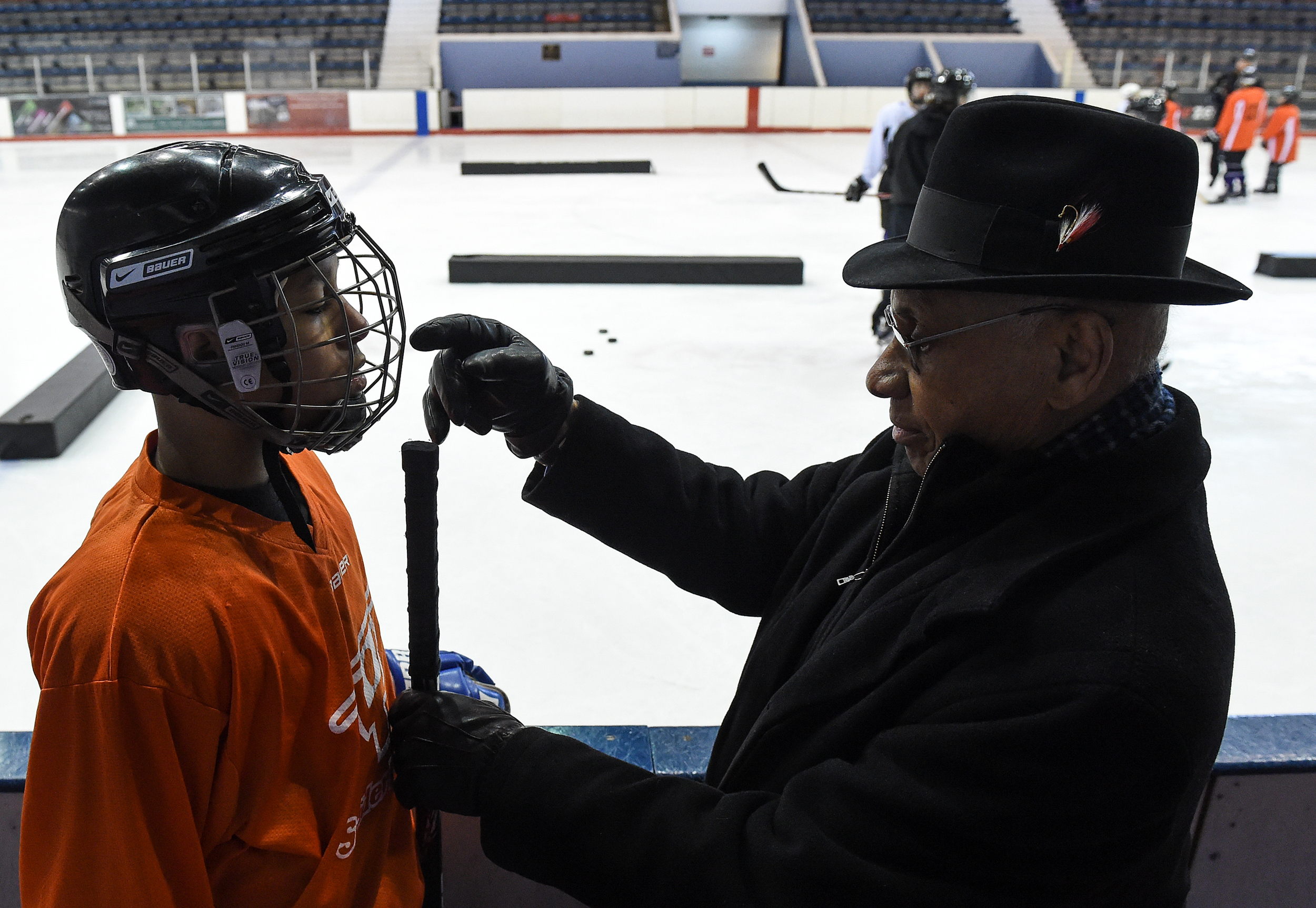 Willie O'Ree checks the height of the stick of Jeremiah Alvarado, 13, of Buffalo, New York, during the 2016 NHL/Willie ORee Skills Weekend hosted by the Ed Snider Youth Hockey Foundation in Philadelphia, Pa. on Saturday, March 5, 2016. O'Ree, the first black player in the National Hockey League, made his NHL debut with the Bruins on January 18, 1958.