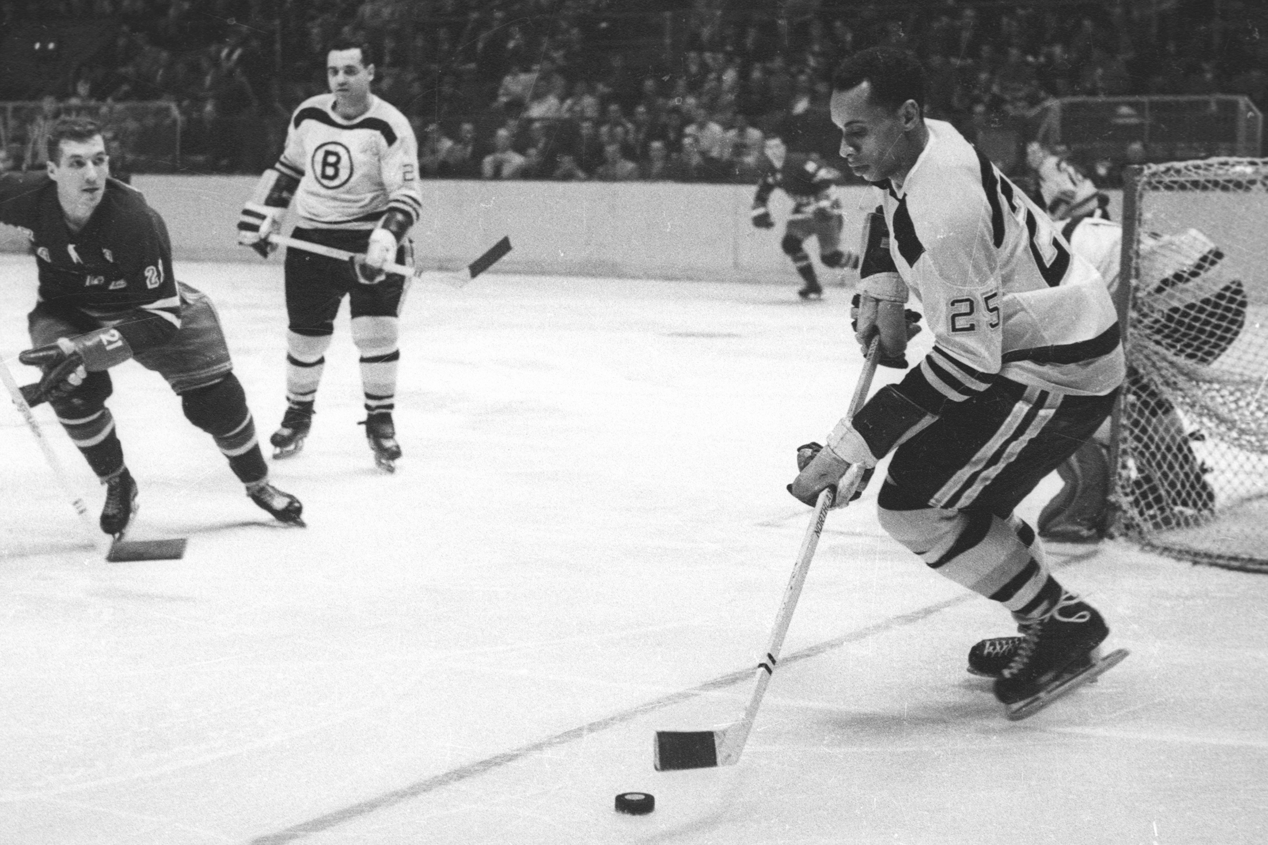 Willie O'Ree #25 of the Boston Bruins skates with the puck as Camille Henry #21 of the New York Rangers looks defend during their NHL game circa 1961 at the Madison Square Garden in New York, New York.