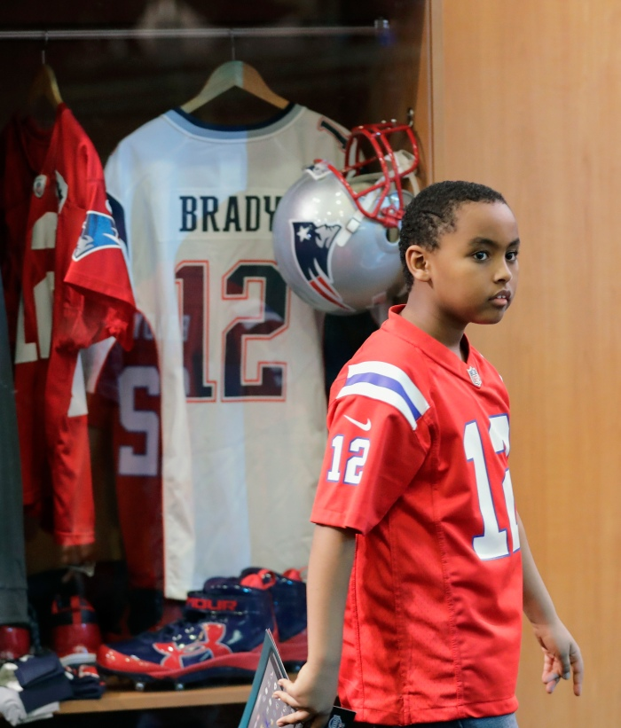 A New England fan walks by replica lockers at the NFL Experience on January  29 92da62142
