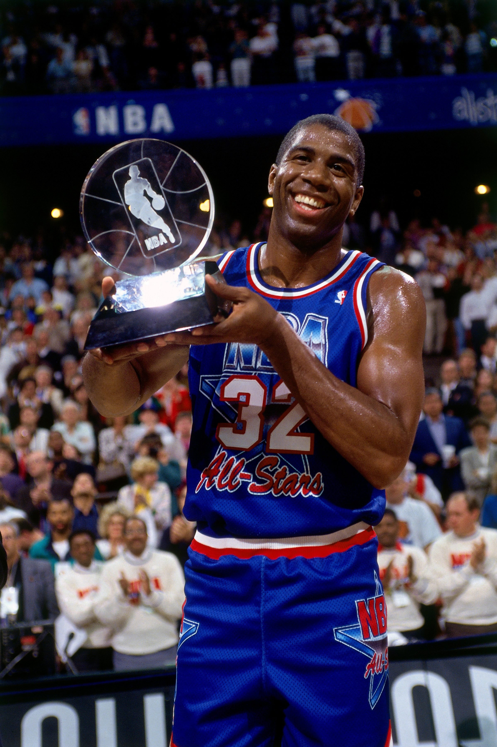 bcab2b01030 Magic Johnson #32 of the Western Conference All-Stars holds the MVP trophy  following