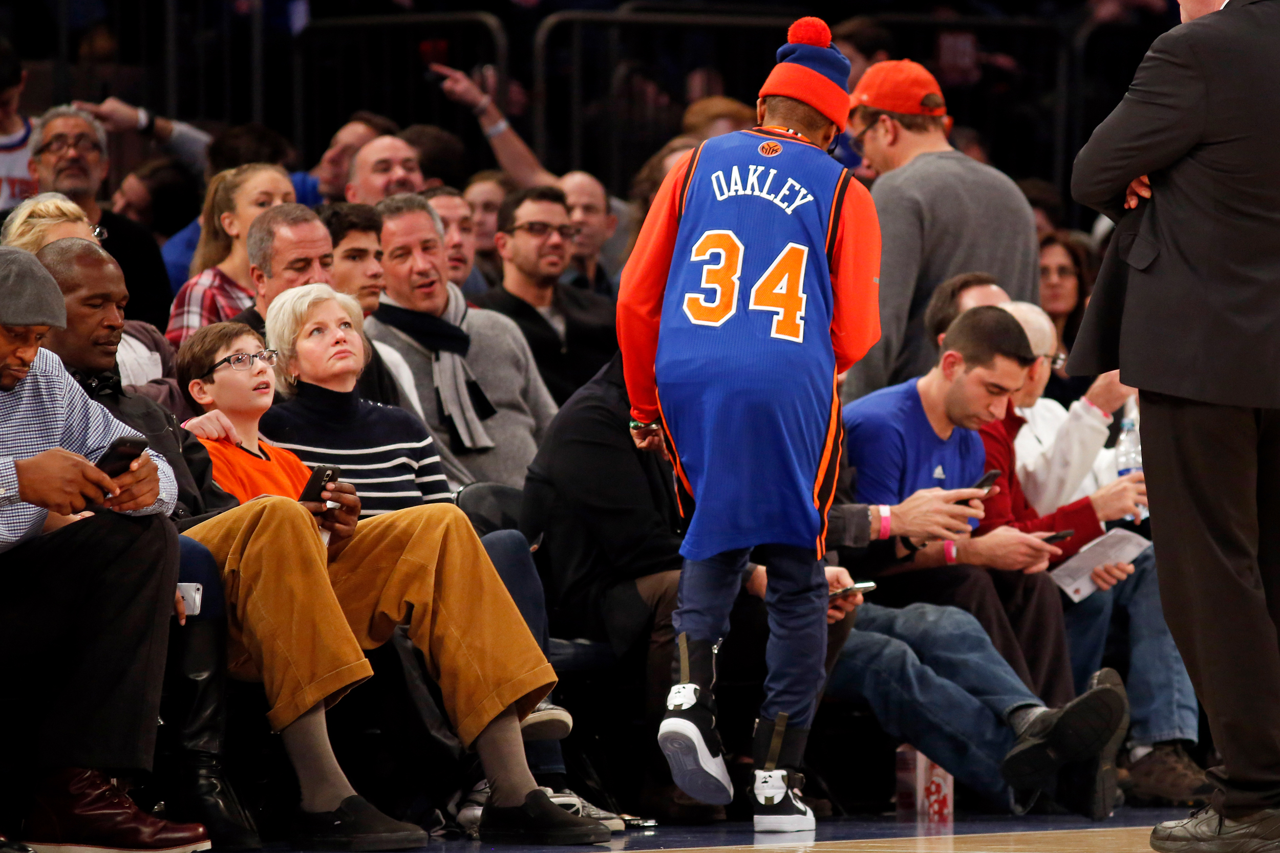 Wearing a Charles Oakley jersey director Spike Lee returns to his seat during the second half against the San Antonio Spurs at Madison Square Garden.