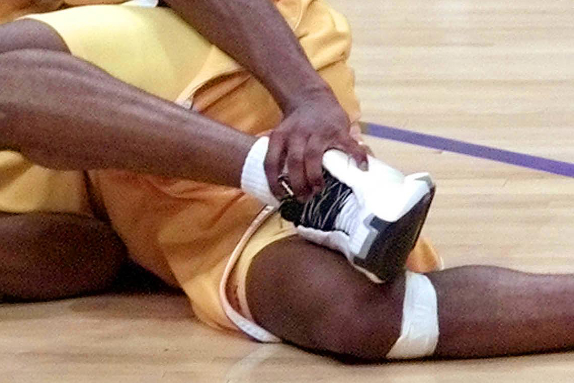 7d6189c16d5 Kobe Bryant of the Los Angeles Lakers holds his injured ankle after  becoming tangled up with Jalen Rose of the Indiana Pacers