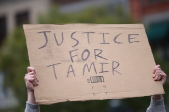 Justice for Tamir sign held aloft. Stop Mass Incarcerations