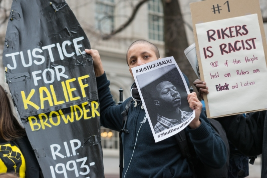 Demonstrators hold aloft a symbolic coffin bearing Kalief