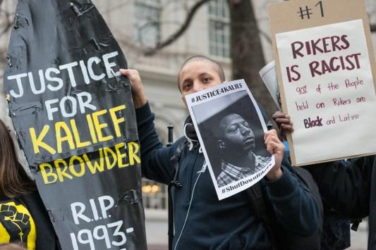 Demonstrators hold aloft a symbolic coffin bearing Kalief