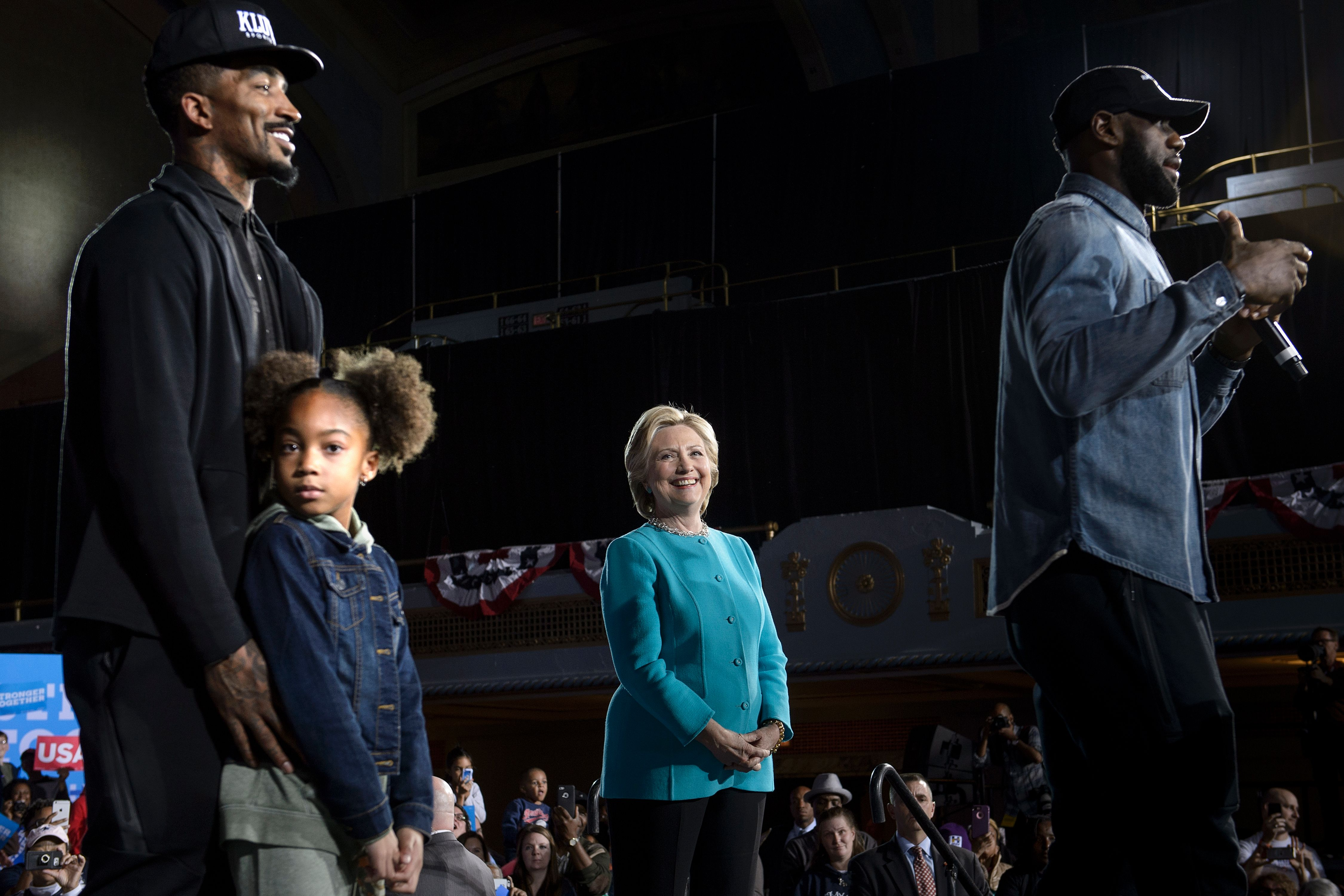252fce684a06d7 Cleveland Cavaliers  guard J. R. Smith (L) and Democratic presidential  nominee Hillary Clinton (2R) listen as Smith s teammate Lebron James speaks  during a ...